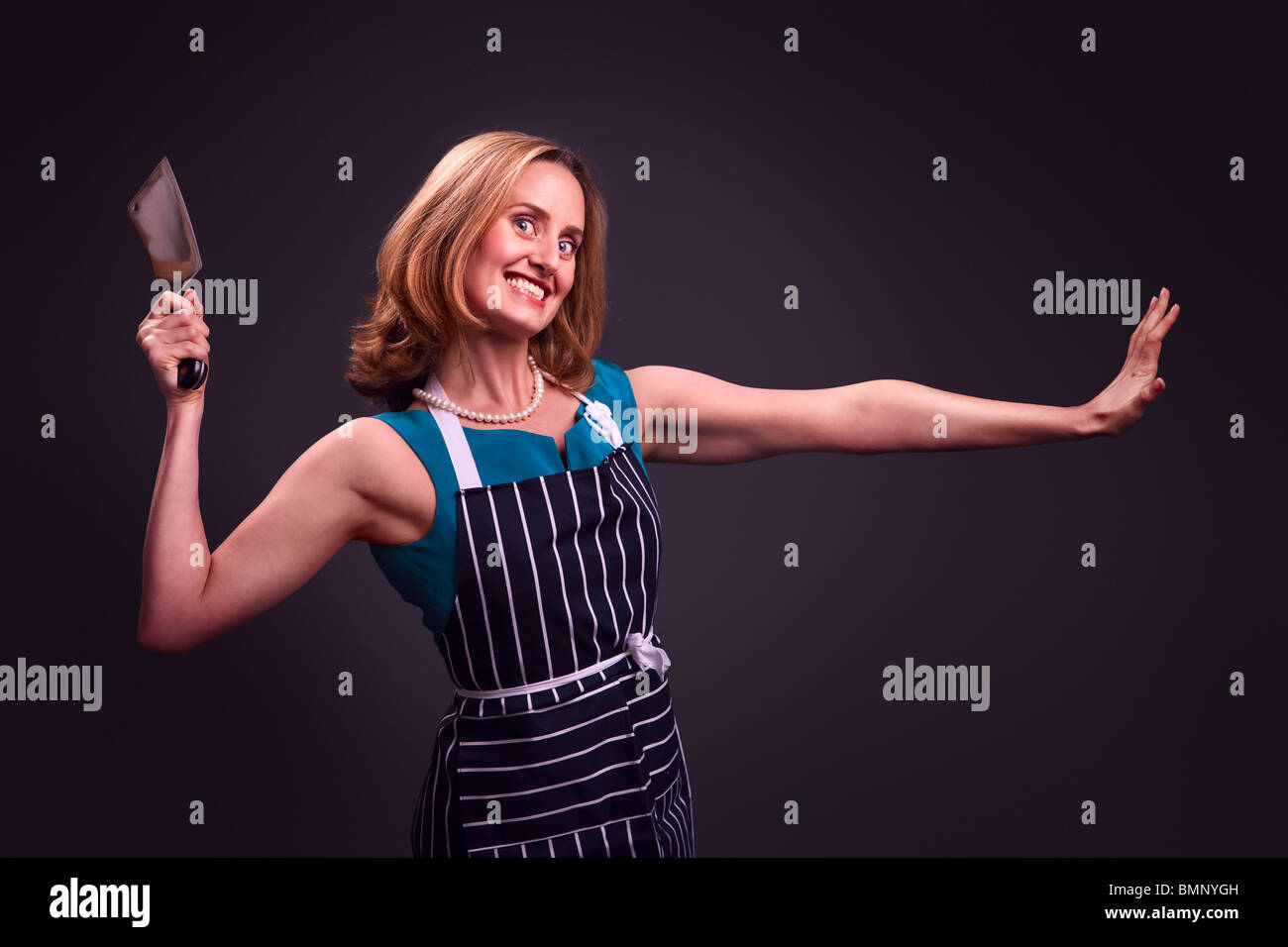 Glamorous housewife wearing butcher's apron and holding meat cleaver - Stock Image