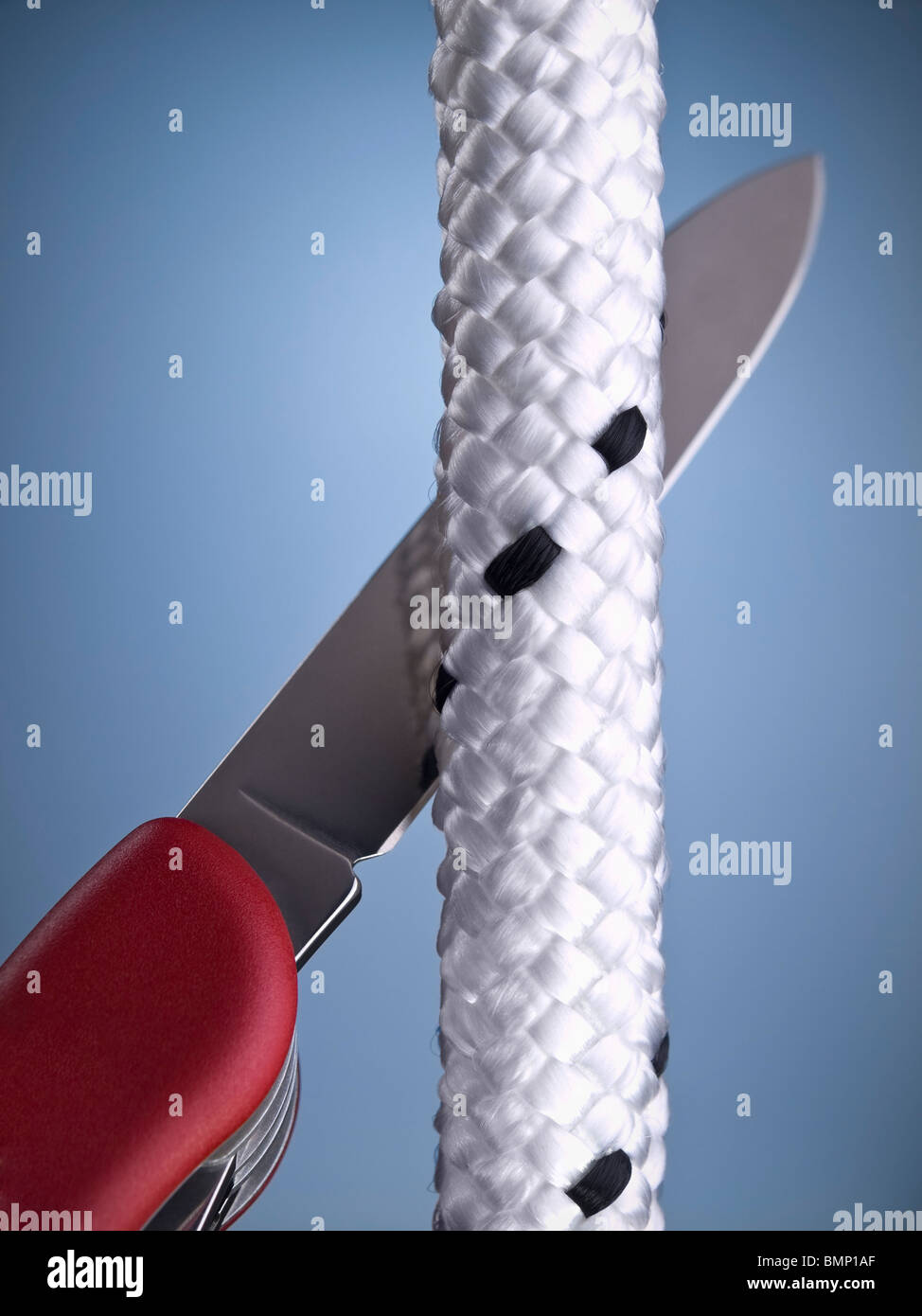 A red Swiss army knife is about to cut a fiber rope. - Stock Image
