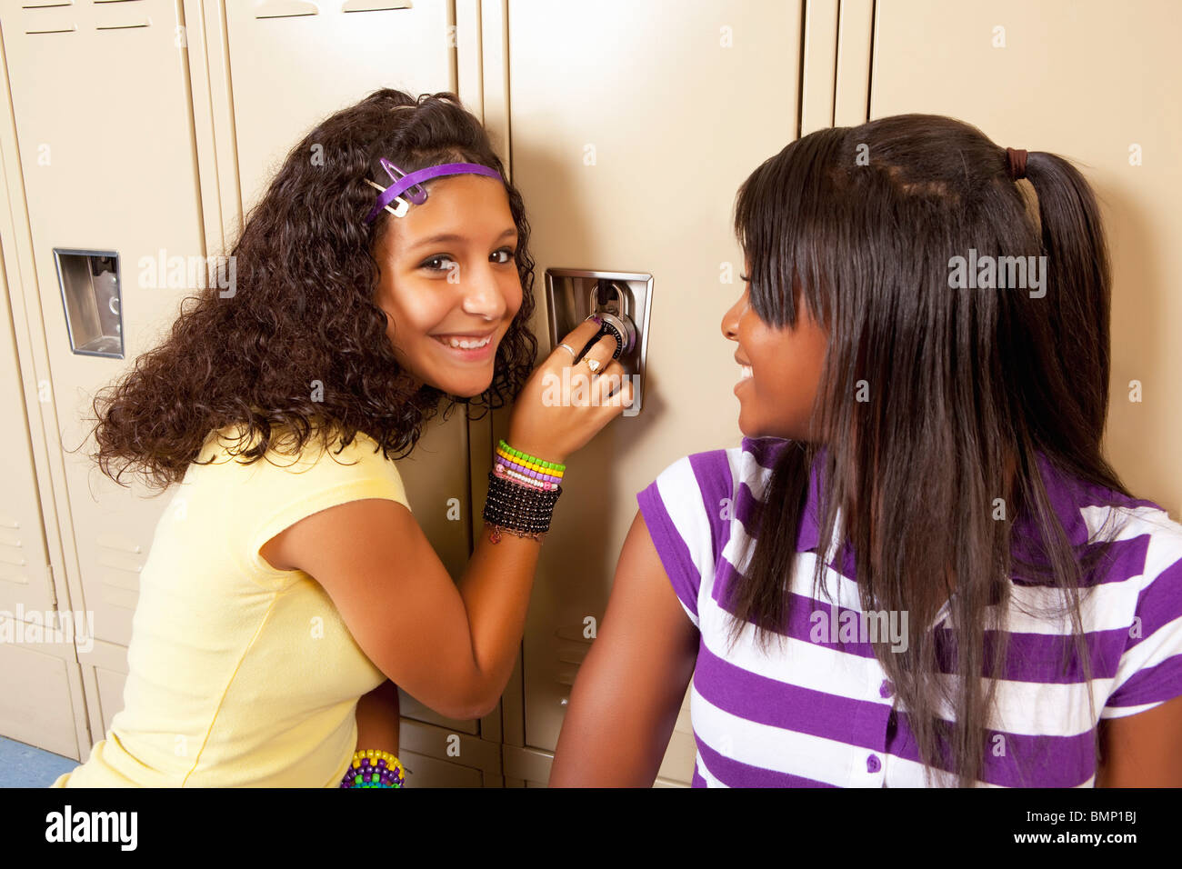 Fort Lauderdale, Florida, United States Of America; Two Teenage Girls Sitting In Hallway Doing The Combination Lock - Stock Image