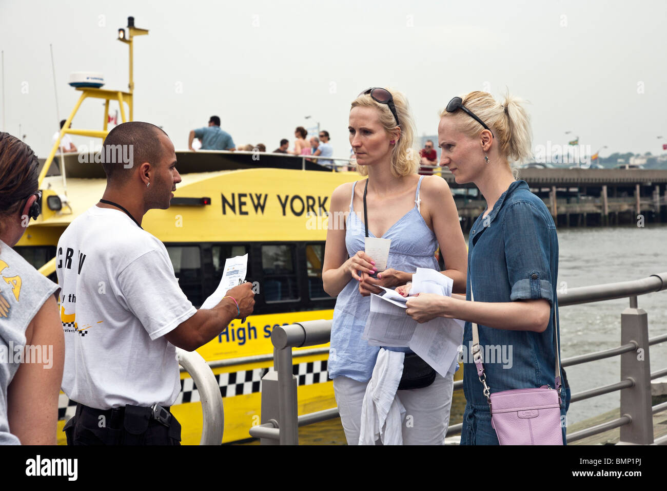 two very blond Nordic tourist sisters embark from Manhattan pier on New York Water Taxi tour of Manhattan waterfront - Stock Image