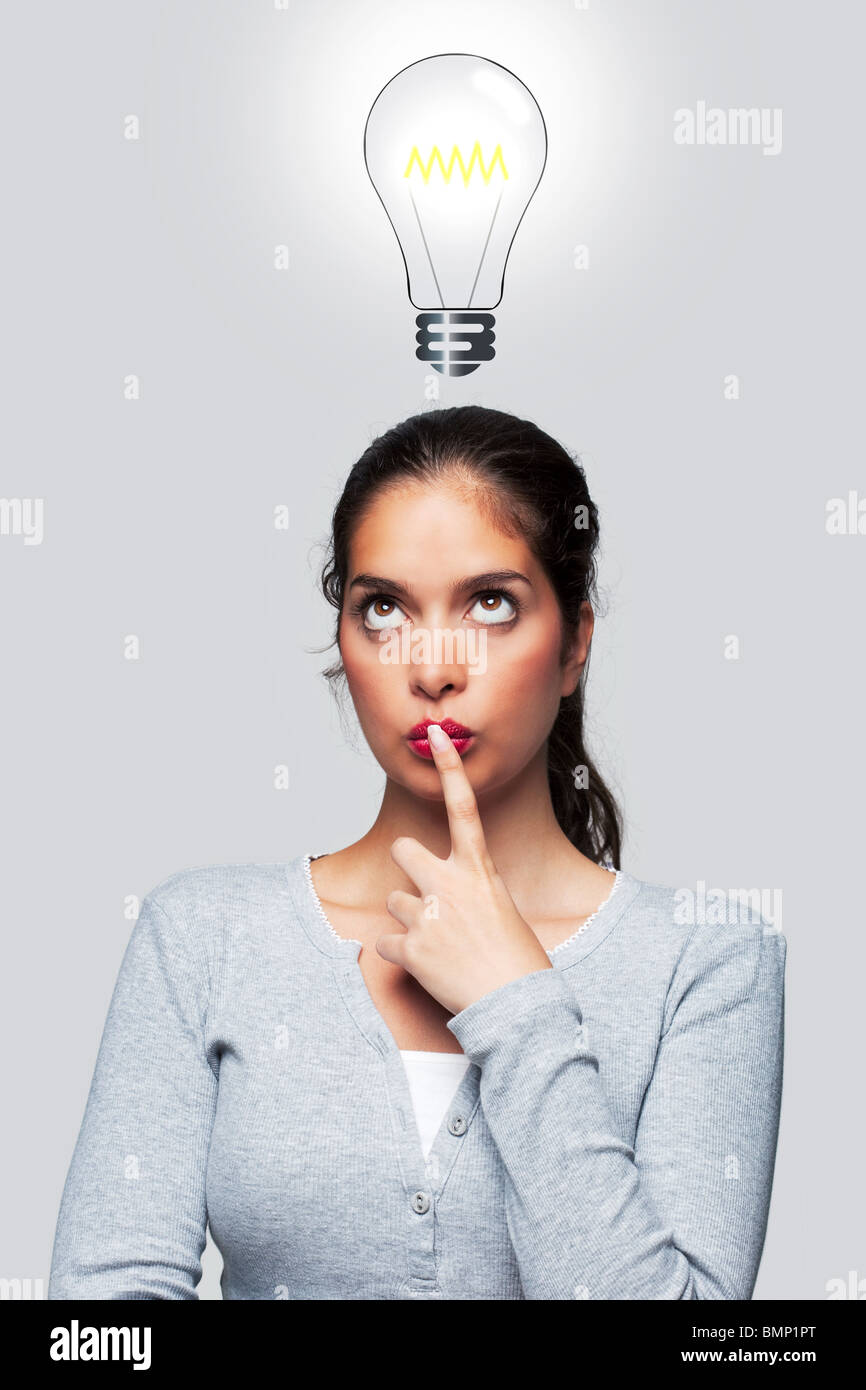 Concept image of a woman with a bright idea, illustration of a lightbulb above her head. - Stock Image