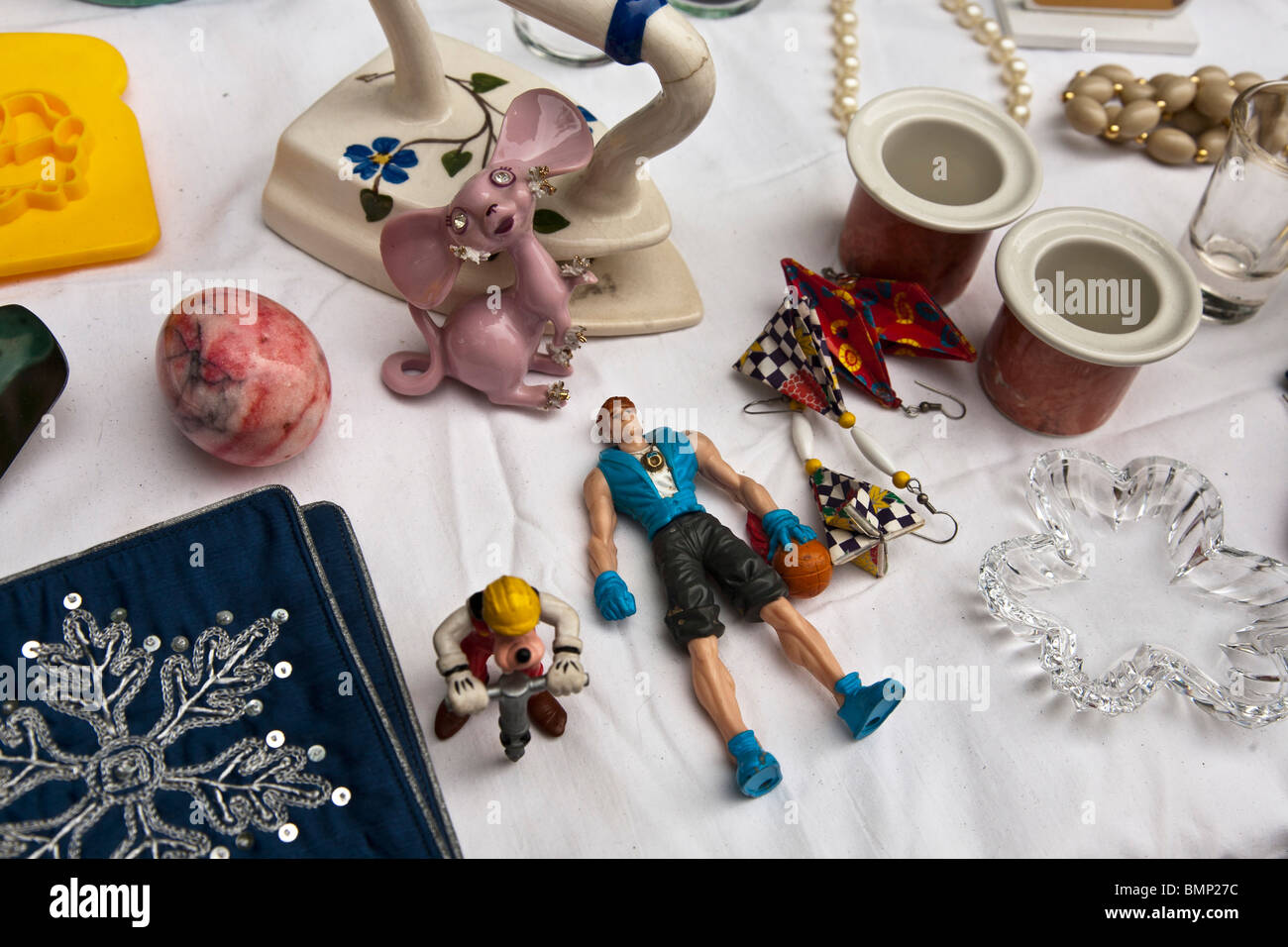 kitsch treasures including marble egg origami earrings & pink mouse with rhinestone eyes displayed for sale - Stock Image
