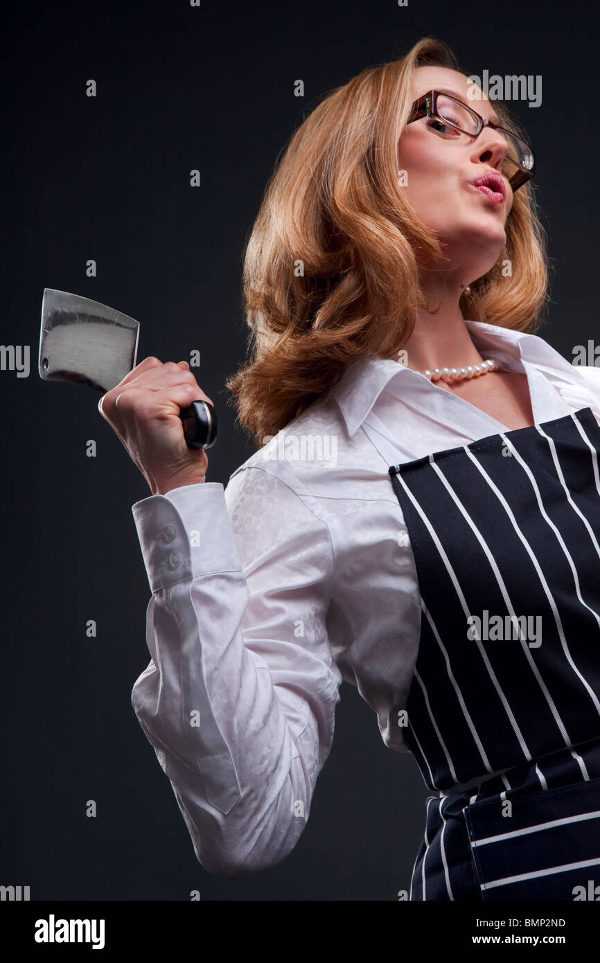 Woman holding meat cleaver wearing butcher's apron against a dark background - Stock Image