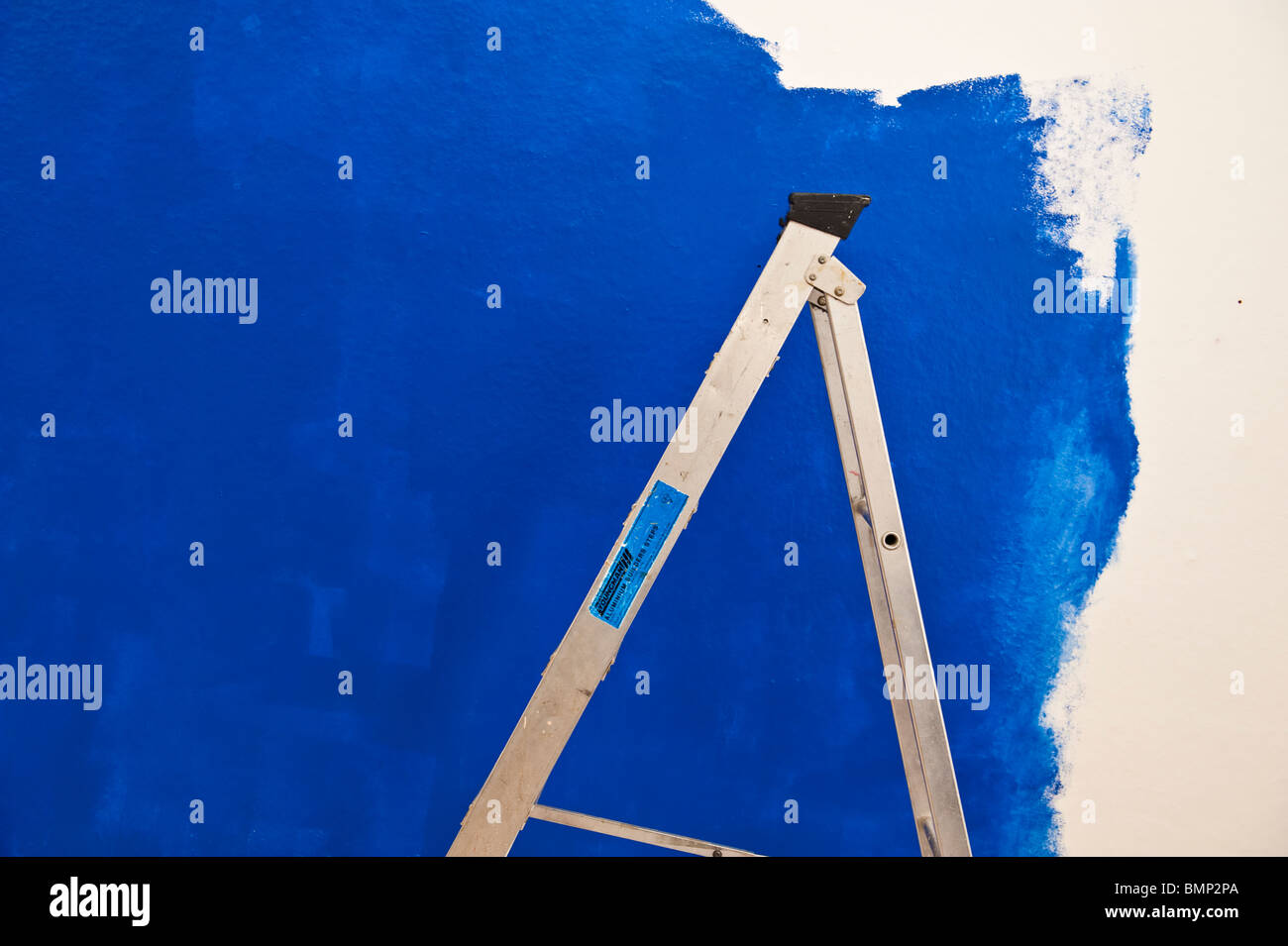 a stepladder and an unfinished blue painted wall Stock Photo