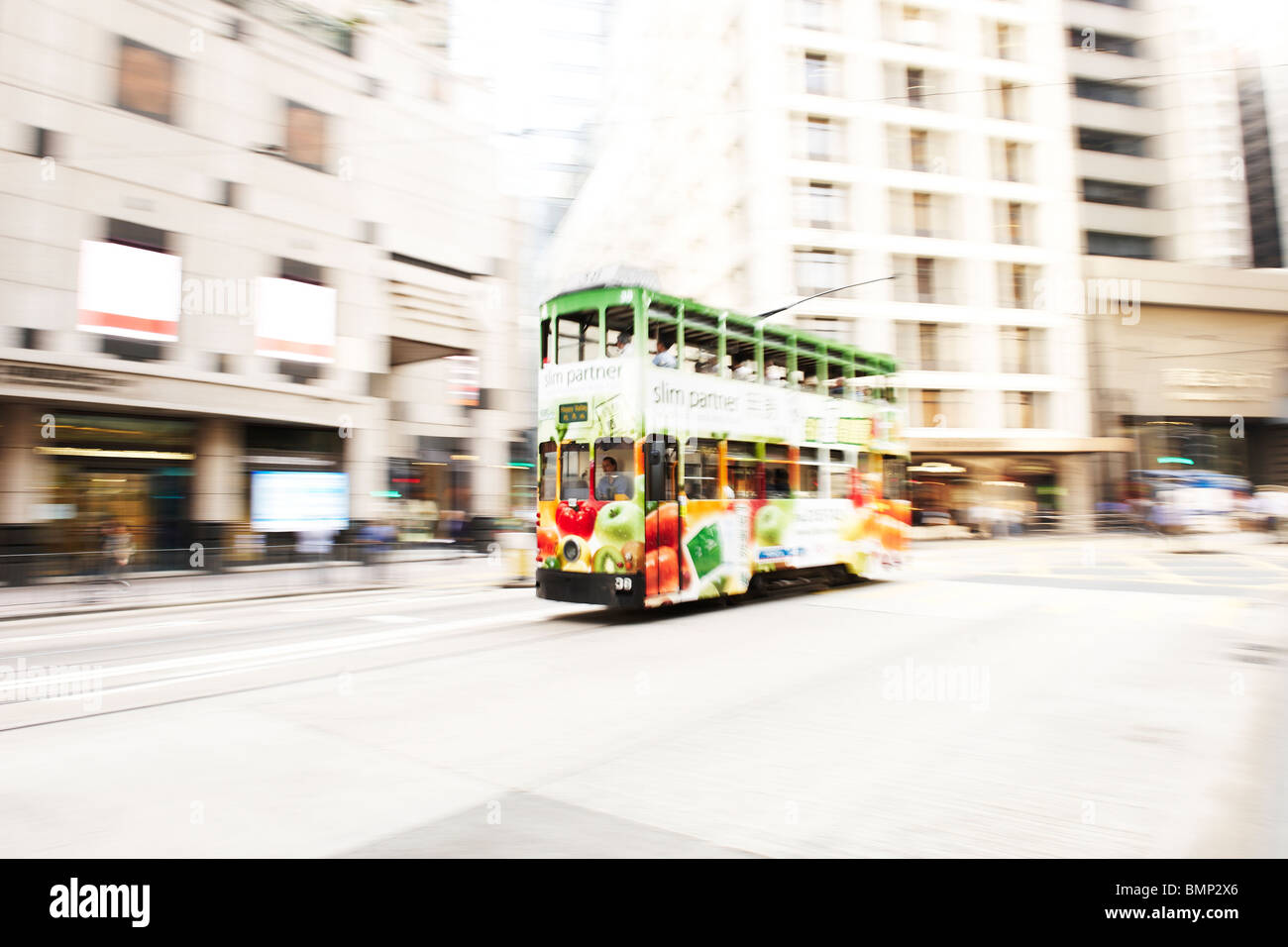 A double decker bus covered in colorful advert move across downtown Hong Kong, captured with motion blur. - Stock Image