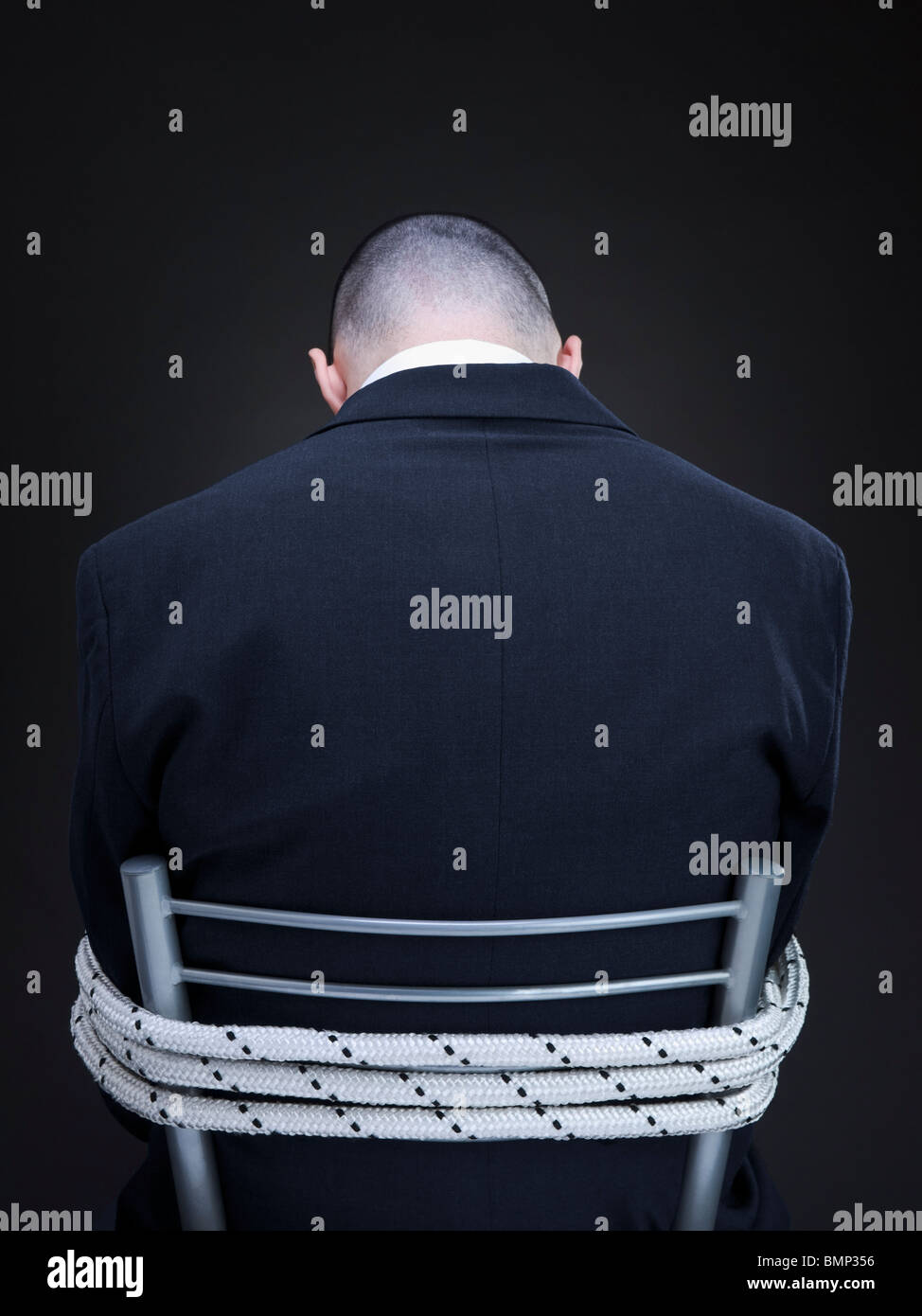 A businessman is tied up on a chair turning his back to the camera. Stock Photo