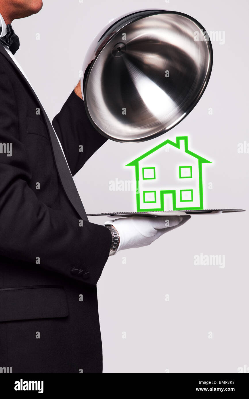 Butler lifting the cloche from a silver serving tray to reveal a house illustration, good image for housing themes. - Stock Image