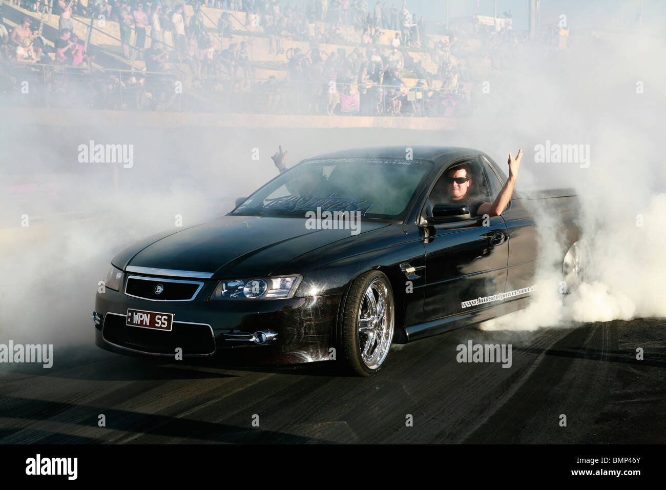 Holden utility or pick up truck performing a massive tyre tire smoking burnout at an Australian lifestyle car show - Stock Image