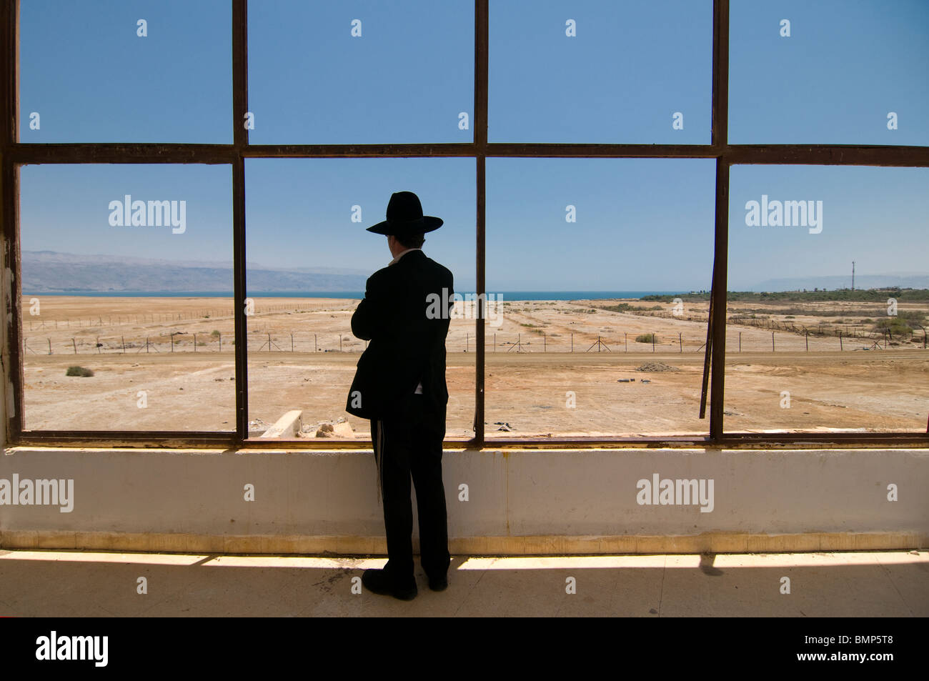 An Ultra orthodox  religious Jew peers out the window of the deserted Lido hotel complex in the northern shore of - Stock Image