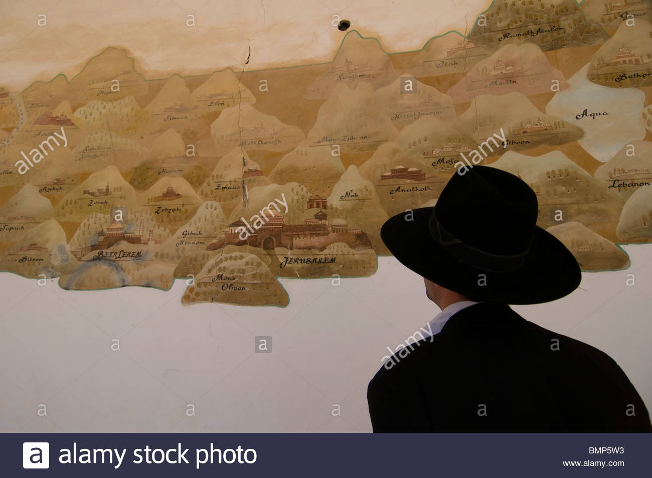 Ultra orthodox Jew observing a wall painting depicting old map of the holyland in an abandoned structure at the - Stock Image