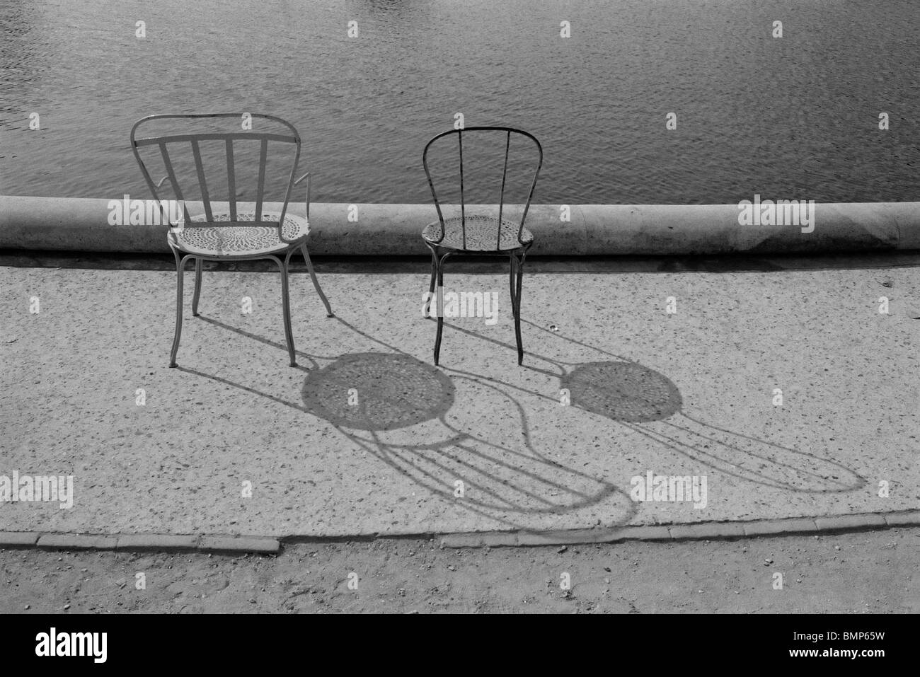 A black and white photograph of two chairs in the Tuileries Gardens,Paris, France. - Stock Image