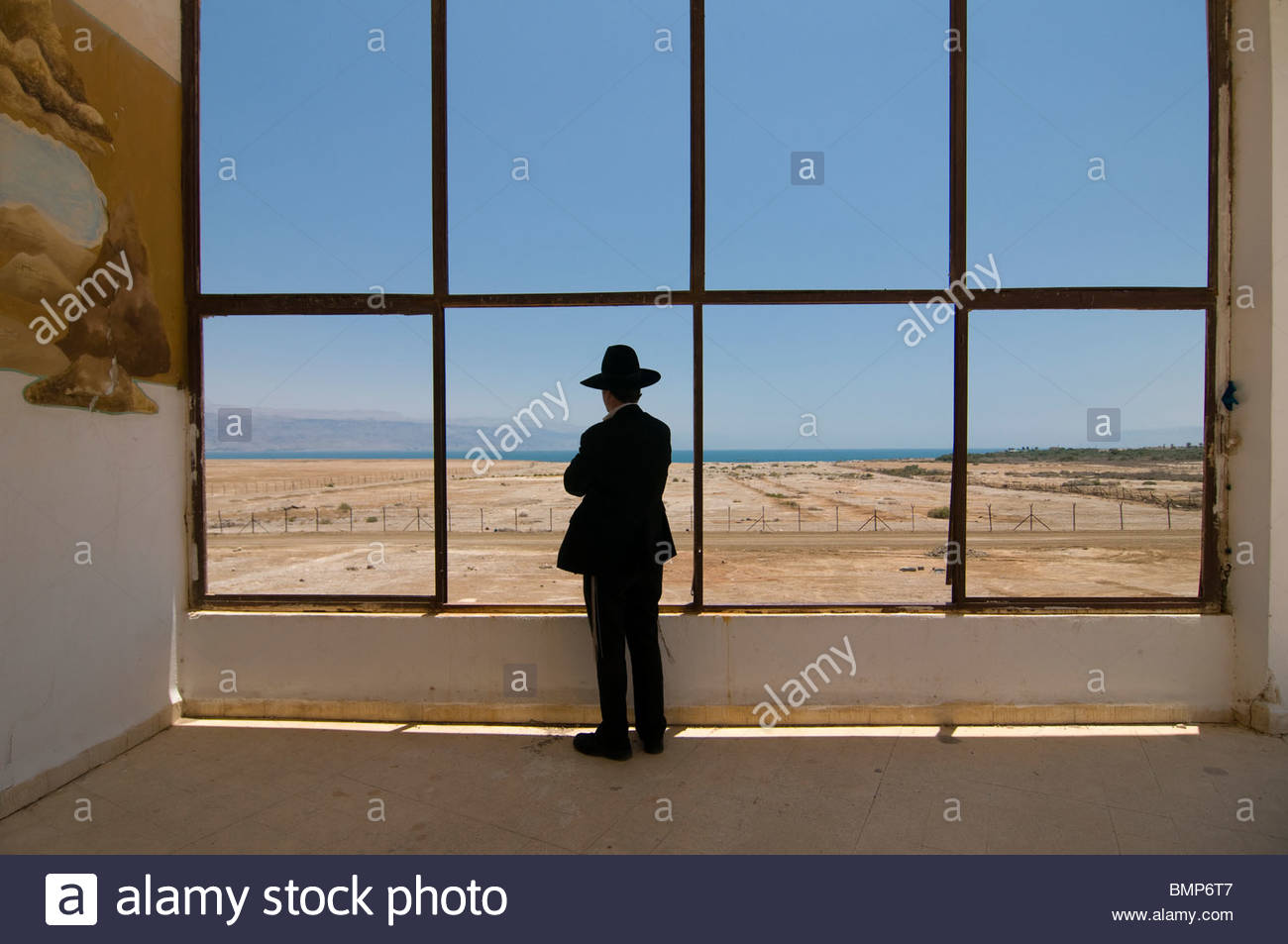 An Ultra orthodox  religious Jew peers out a window of the deserted Lido hotel complex in the northern shore of - Stock Image