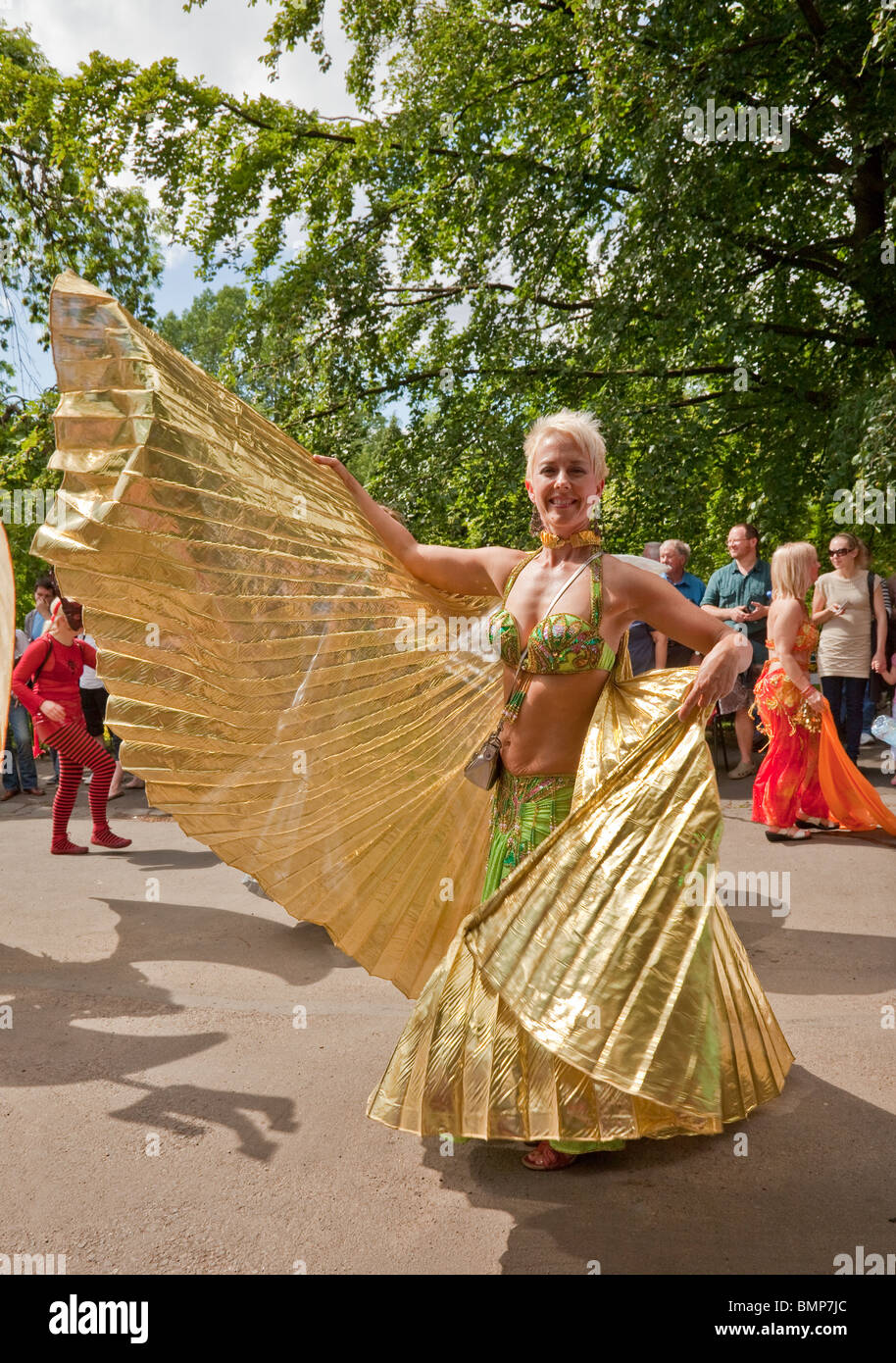 Woman shows off her golden costume at Glasgow's West End Festival Sunday Parade, 2010, in Kelvingrove Park. - Stock Image
