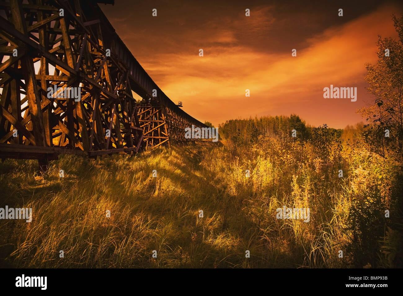 Alberta, Canada; A Train Trestle In A Sunset Stock Photo