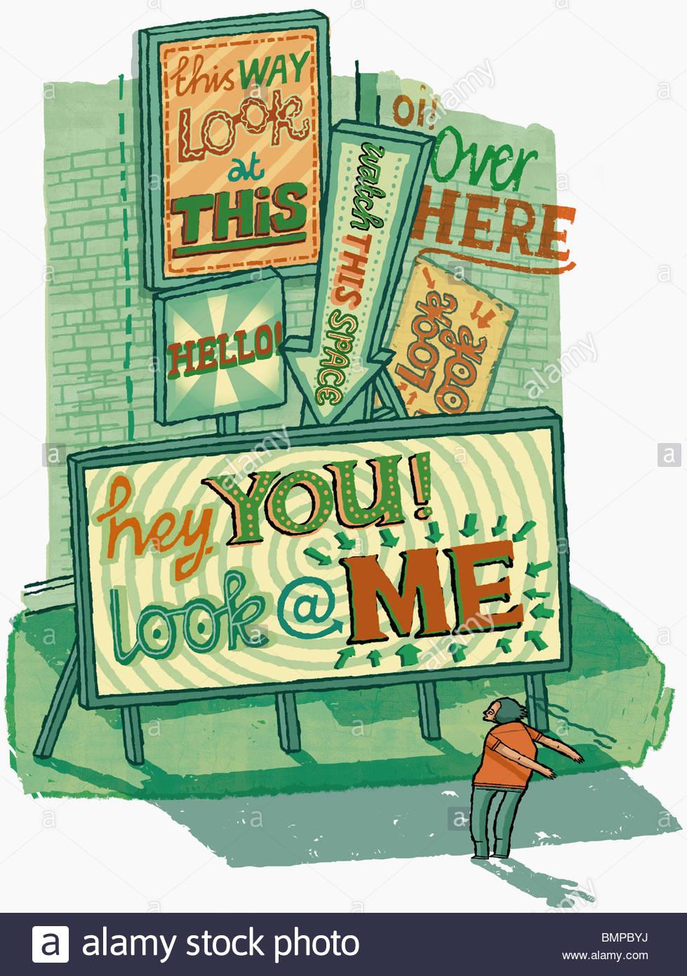 Man standing below billboards - Stock Image