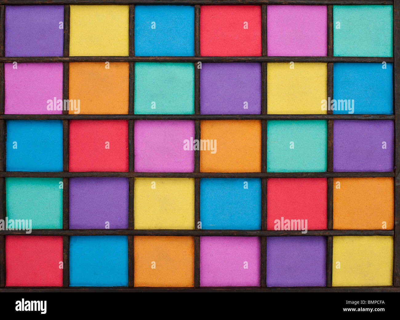 Multicoloured sand pattern in a wooden grid - Stock Image
