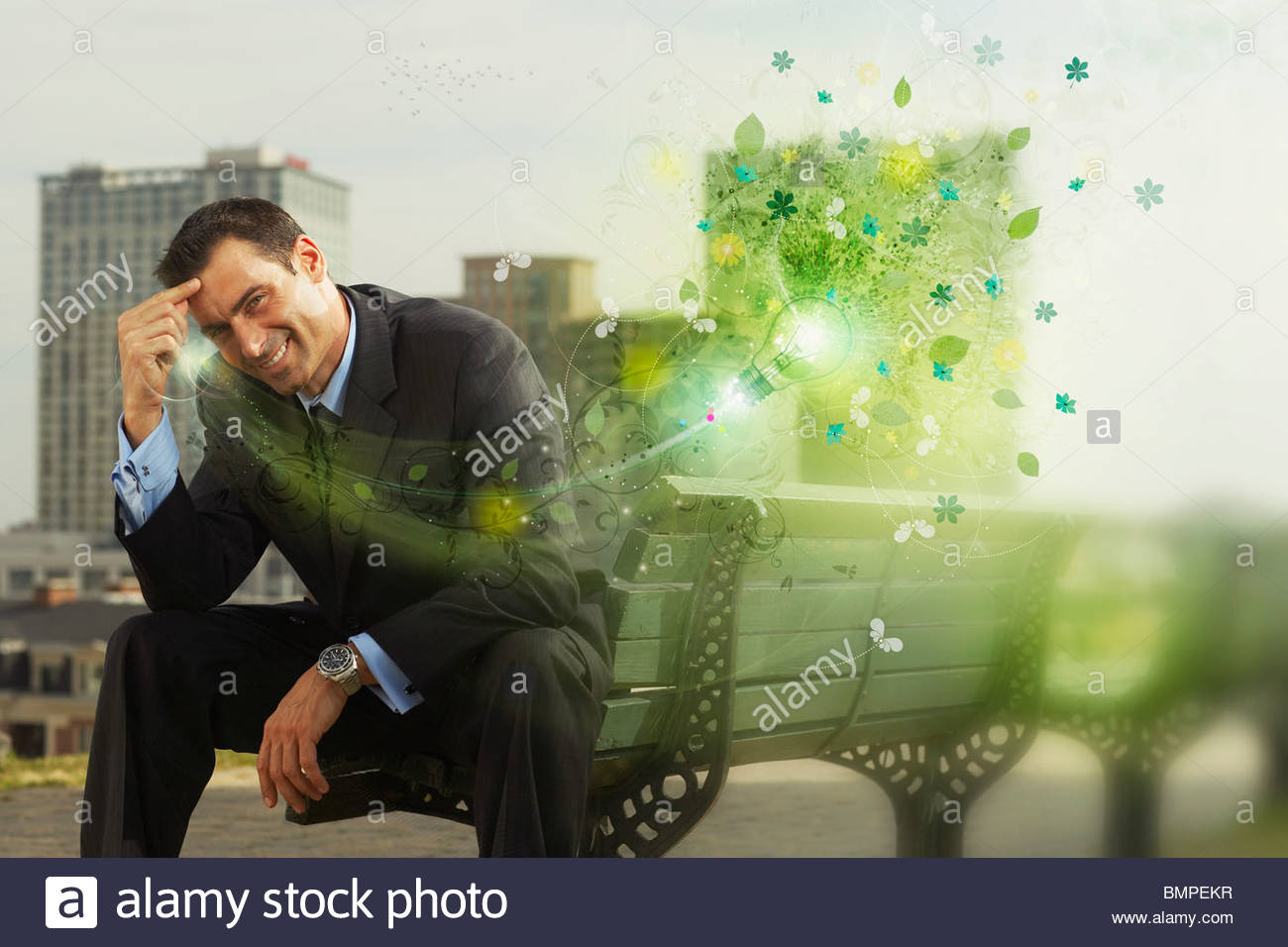 Green graphics emerging from businessman on bench - Stock Image