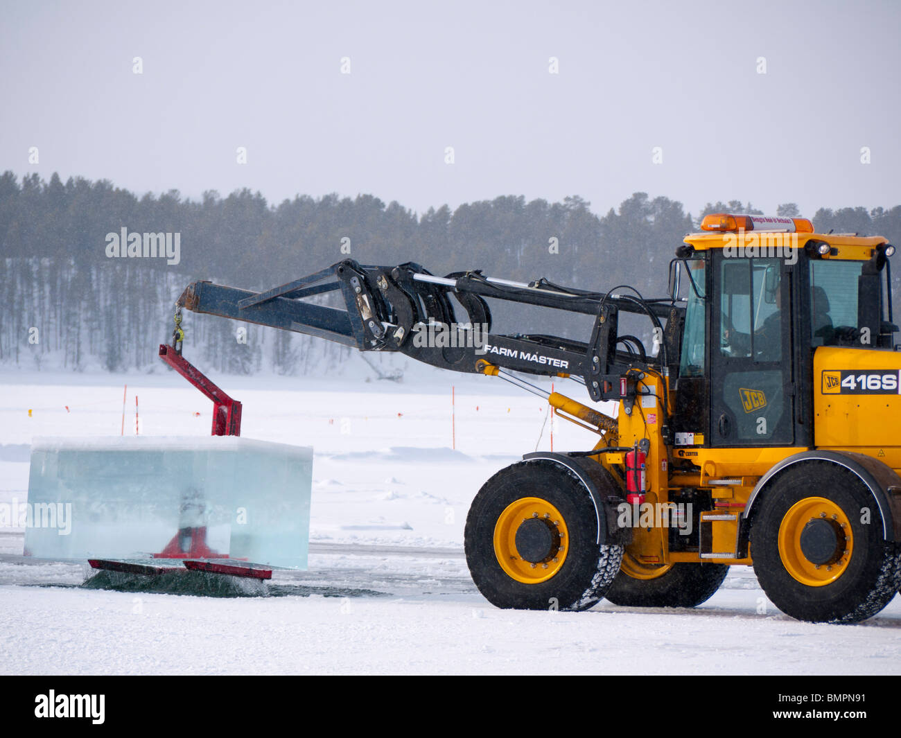 Big blocks of ice are being cut and lifted out from the frozen Torne Älv river with heavy equipment at the - Stock Image