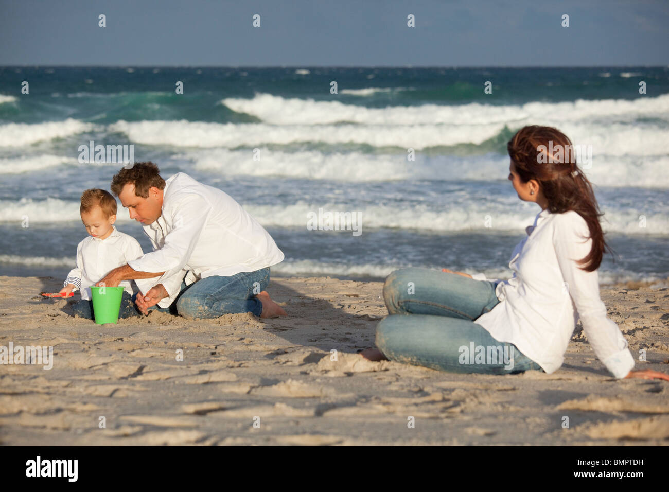 Fort Lauderdale, Florida, United States Of America; A Father And Son Play In The Sand On The Beach While The Mother - Stock Image