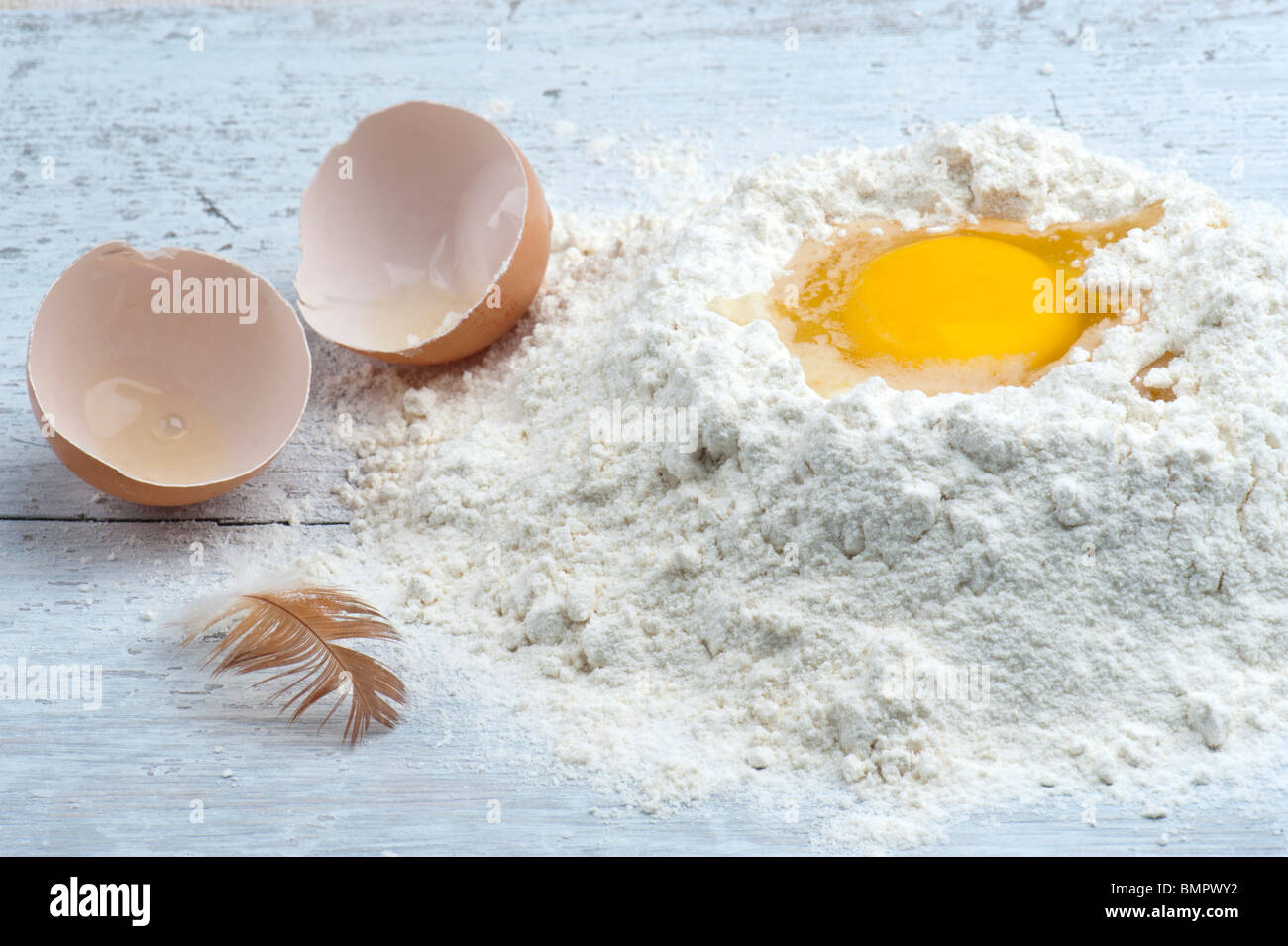A Cracked Egg In Some Flour, With The Shell and A Hen Feather To The Side - Stock Image