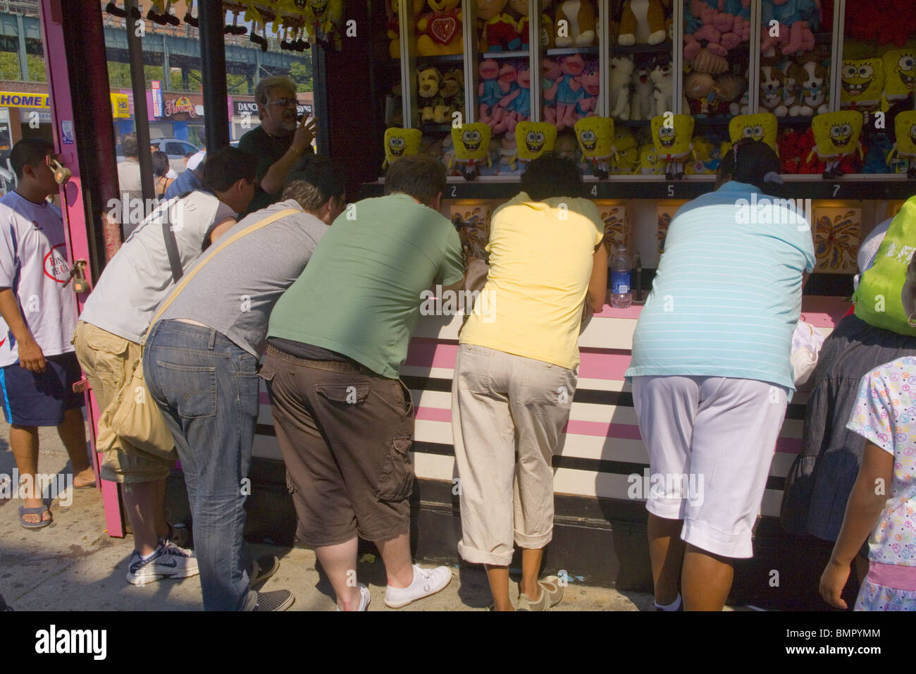 Adults playing a game to win a stuffed animal, Coney Island, Brooklyn, NY. - Stock Image