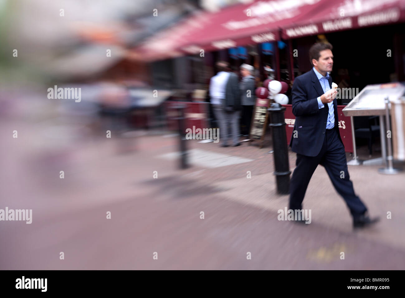 A business man walking with an ice cream in Leicester Square, London, England. - Stock Image