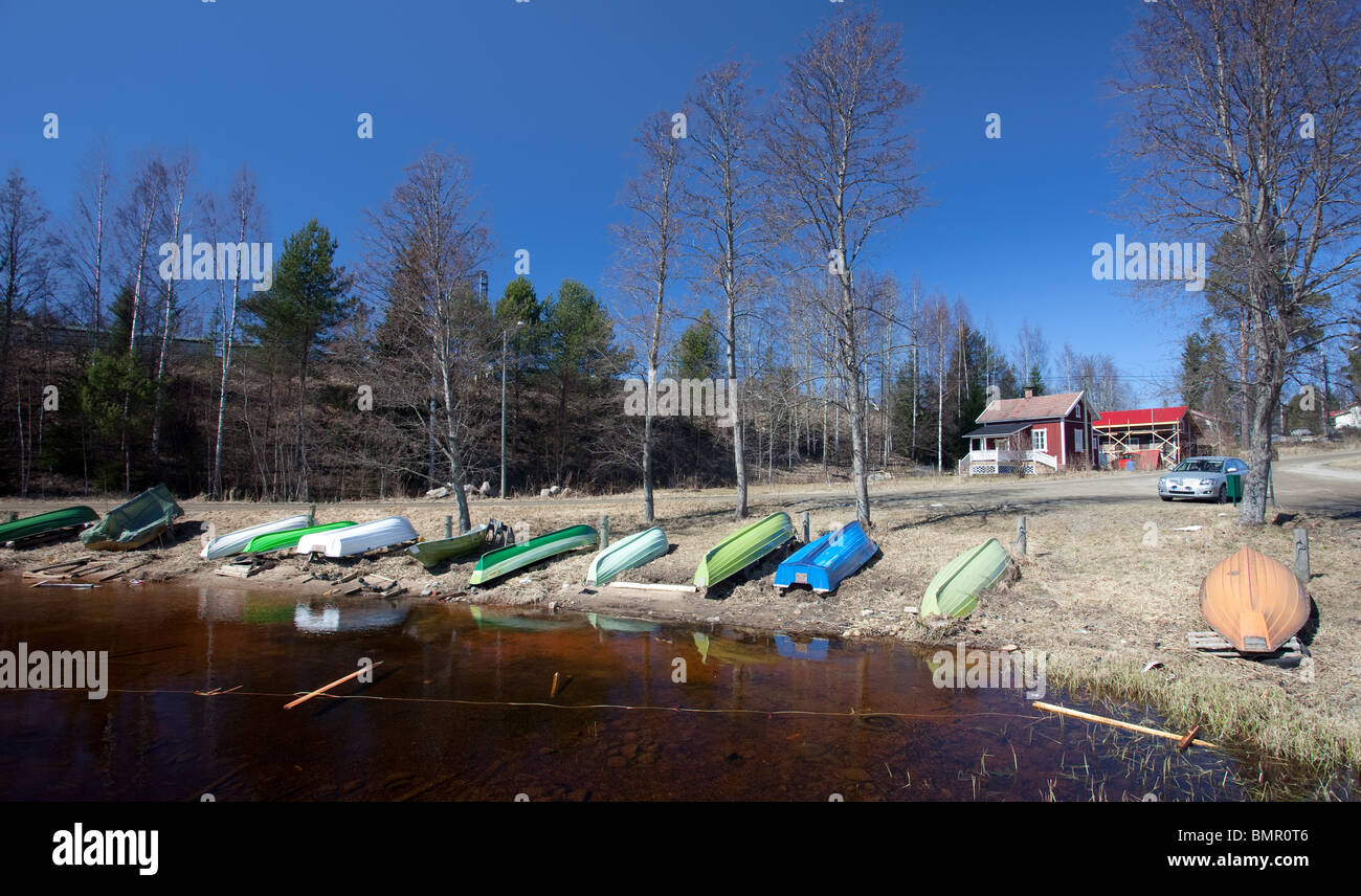 Finnish small boat harbor at countryside at early Spring . Upturned rowboats and skiffs , Finland - Stock Image