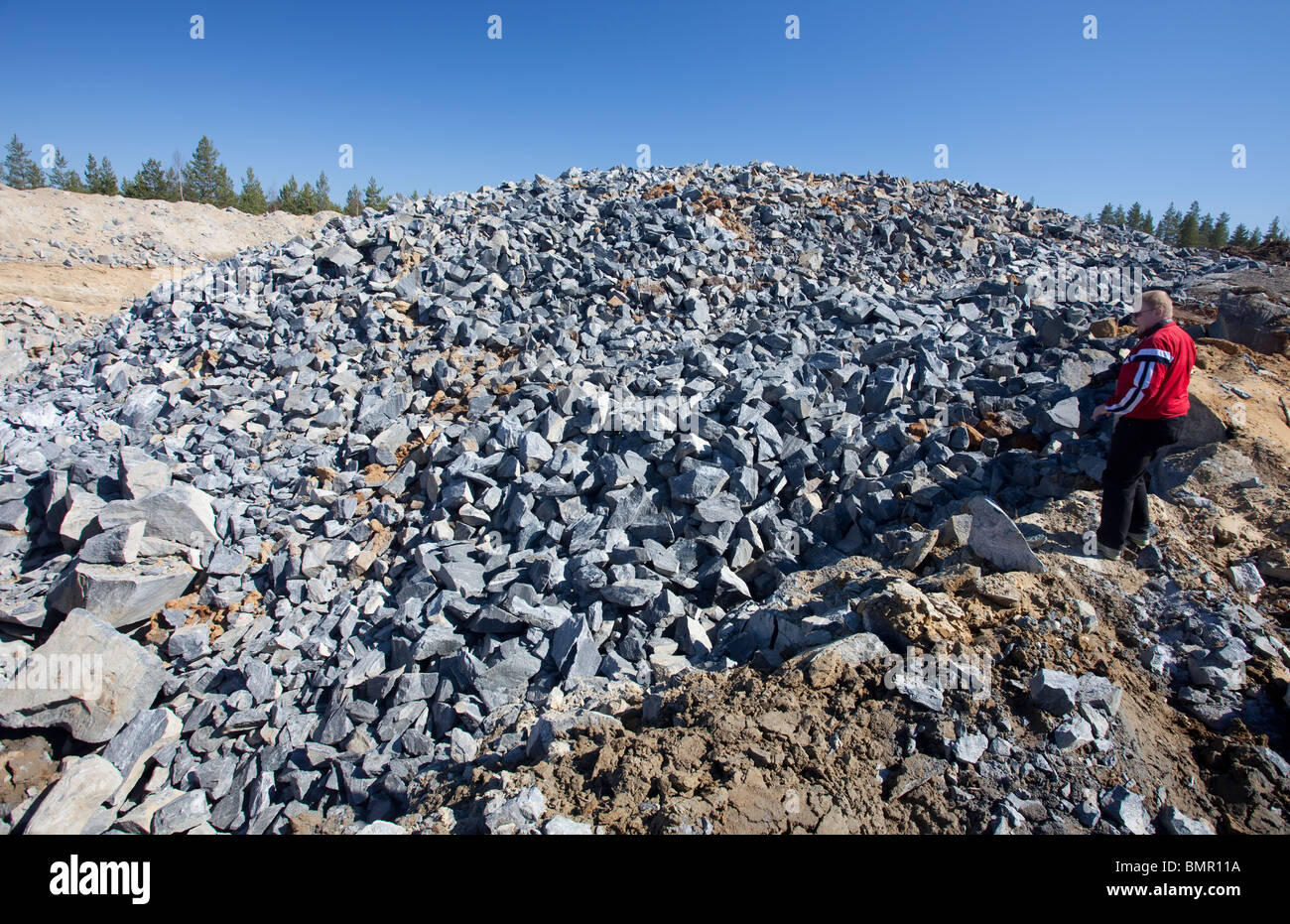 Man watching pile of rocks that were exploded from the bedrock at rock quarry , and later used as raw material , - Stock Image