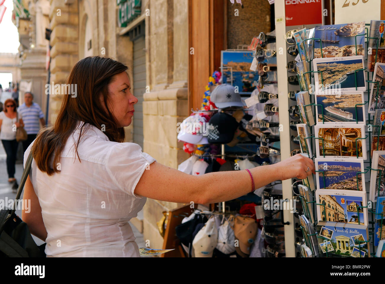 Female tourist browsing postcards in Valletta, Malta. - Stock Image