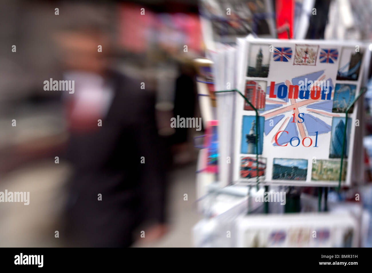 A business man walks past a 'London is cool' set of postcards on Piccadilly in London. - Stock Image