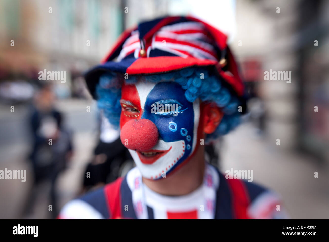 A clown dressed in the colours of the British flag in Piccadilly Circus, London, England. - Stock Image