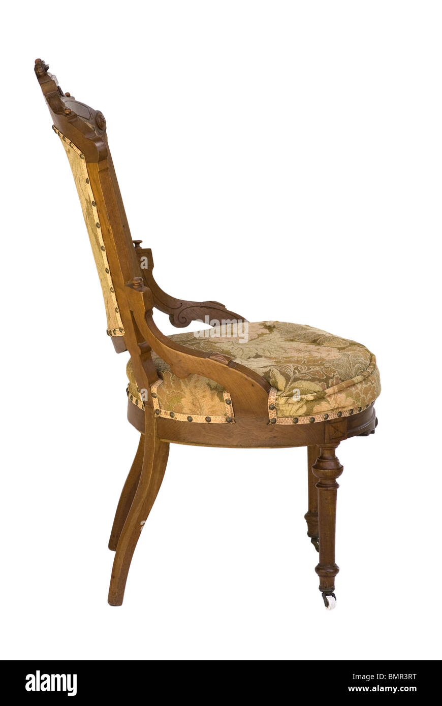 Eastlake Victorian antique wood carved upholstered chair from a side view. Associated with the Victorian era. Isolated - Stock Image