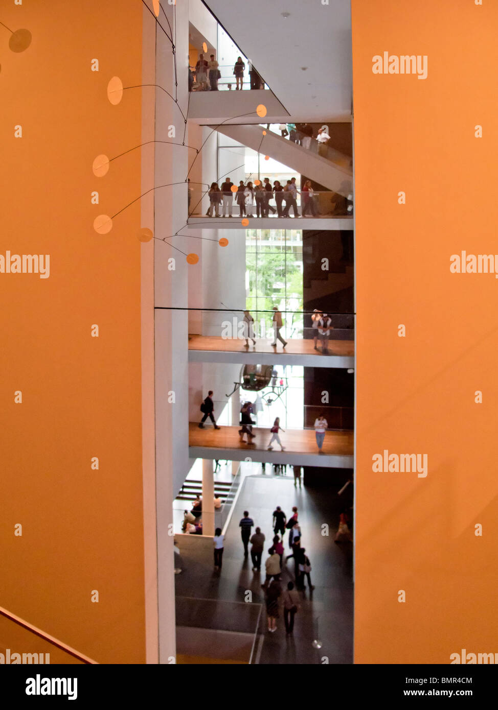 Visitors at the Museum of Modern Art in New York City walk on visible floors. Note Alexander Calder mobile (foreground). - Stock Image