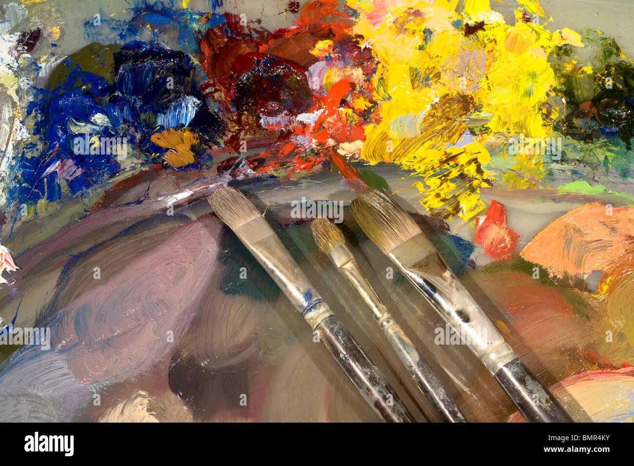 Oil paints on an artist's palette. Note bright colors for emphasis (top) and neutral colors (bottom) for backgrounds. - Stock Image