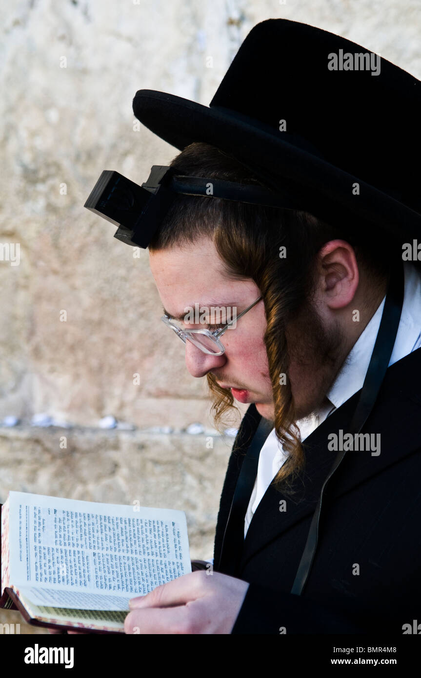A orthodox Jewish man praying by the wailing wall in the old city of Jerusalem. - Stock Image