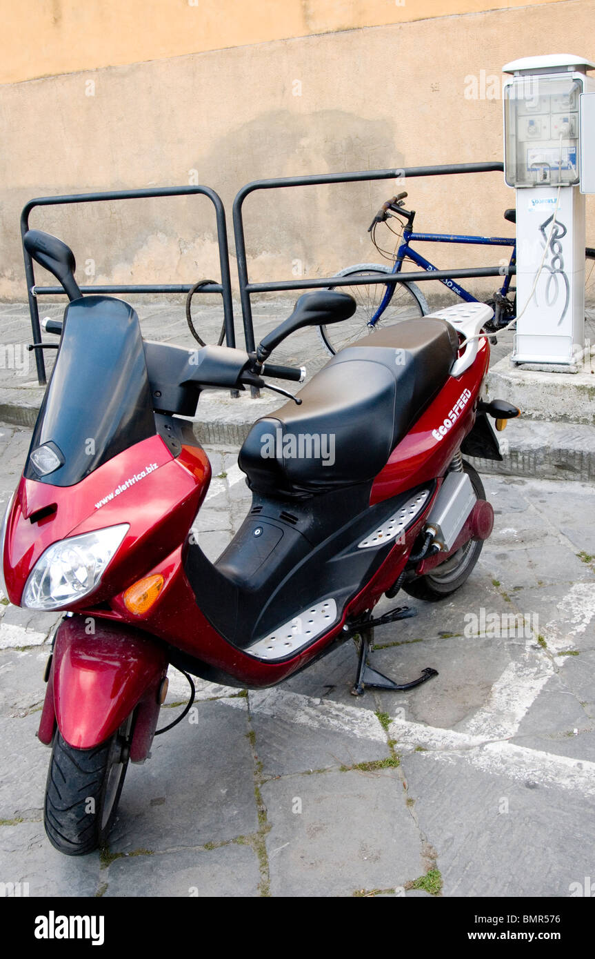 Electric-powered motorcycle receiving a recharge, Florence, Italy - Stock Image