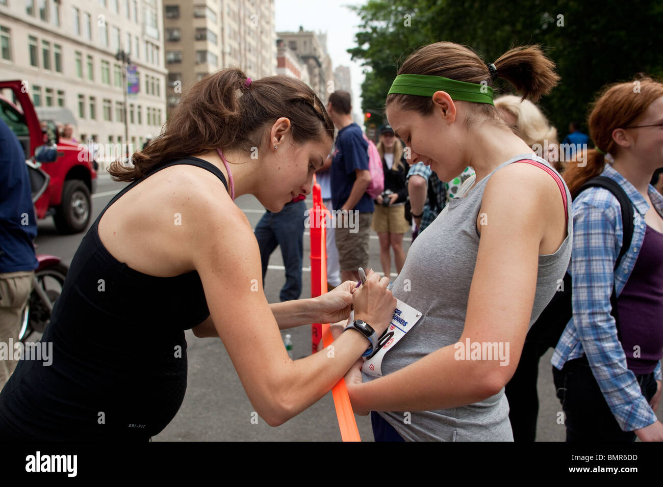 A pregnant Kara Goucher (USA) signing an autograph for a fellow runner at the 2010 New York Mini 10K. - Stock Image