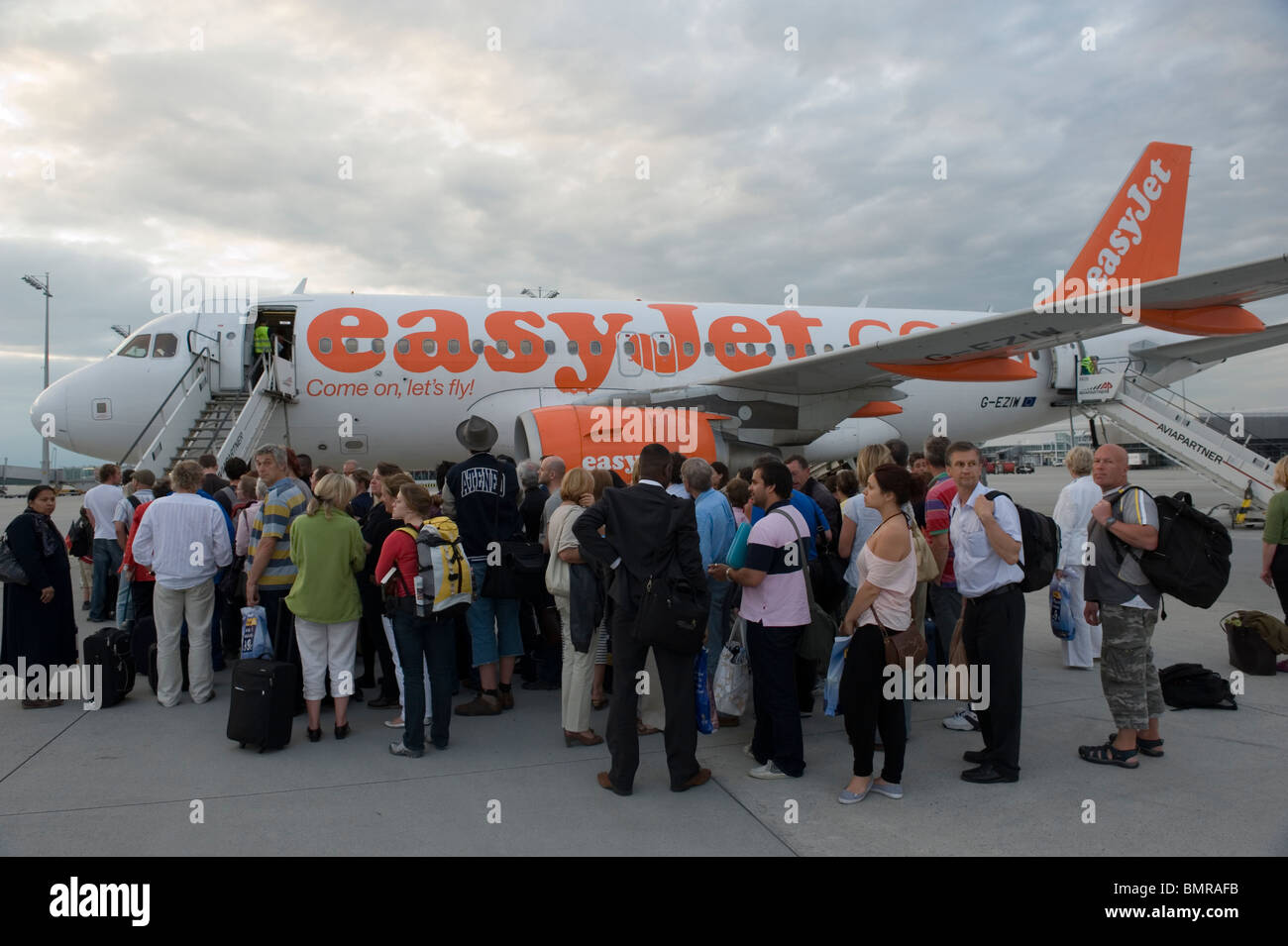 Airline passengers boarding a plane of discount airline Easyjet at Munich airport Germany - Stock Image