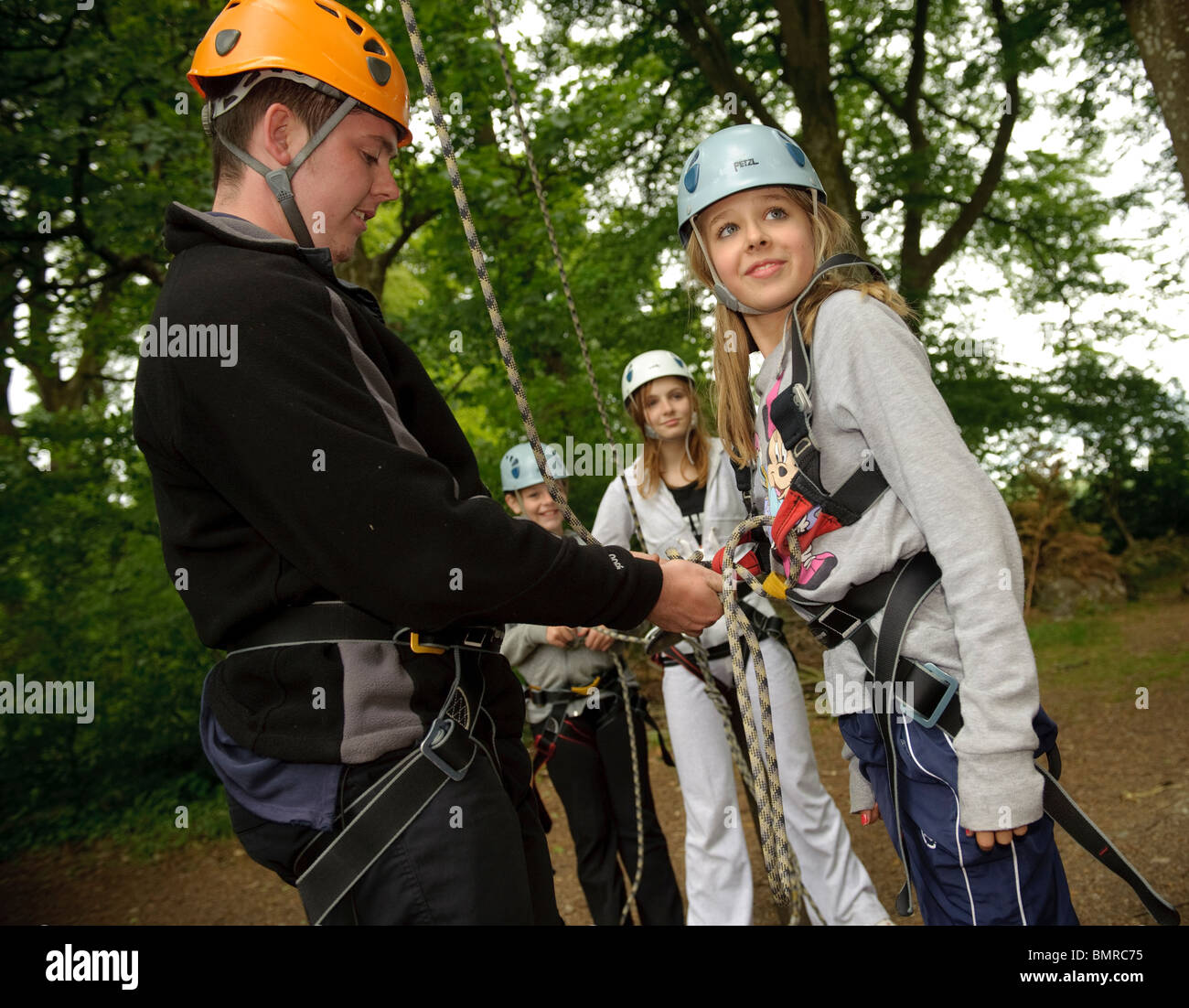 An instructor checking the harness and ropes on a teenage girl as part of a course organised by the Canolfan Yr - Stock Image