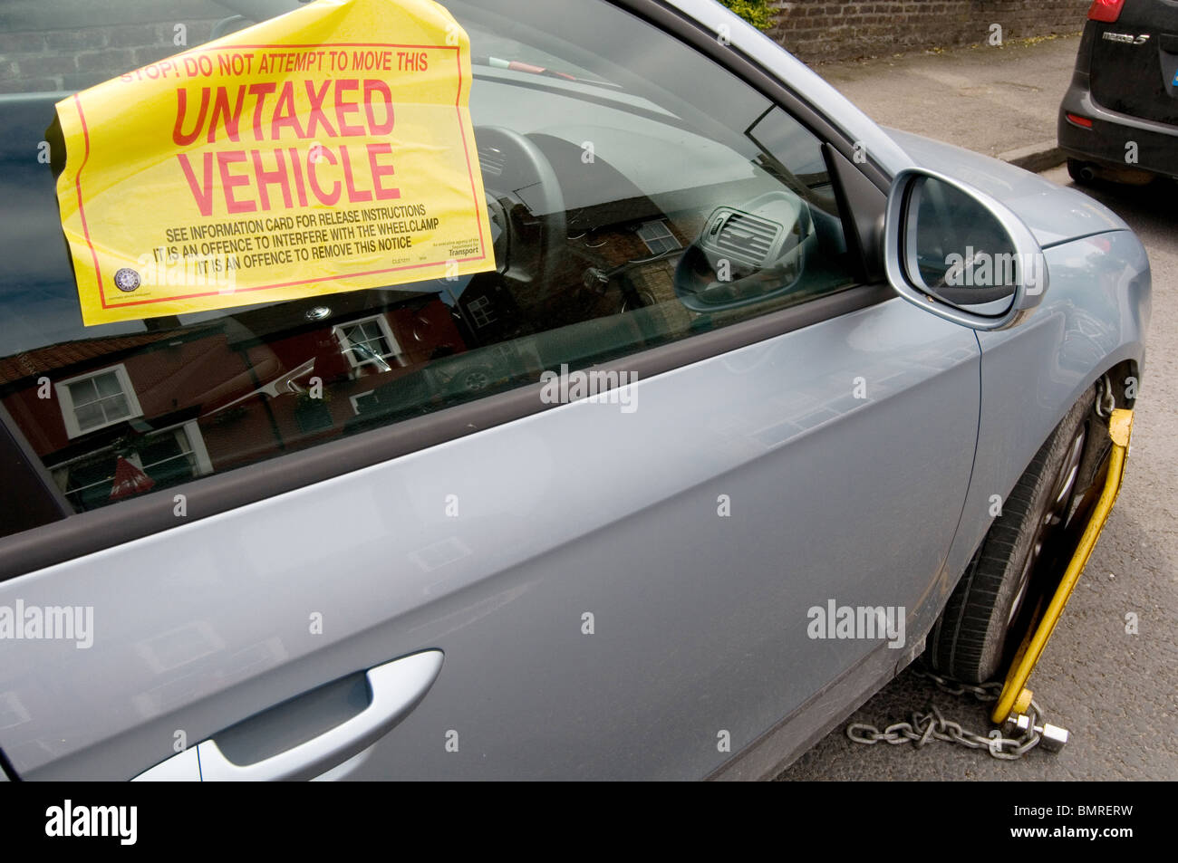 untaxed car tax road avoidance taxation enforcement clamp clamped cars clamping clamper clampers  clamps immobilized Stock Photo