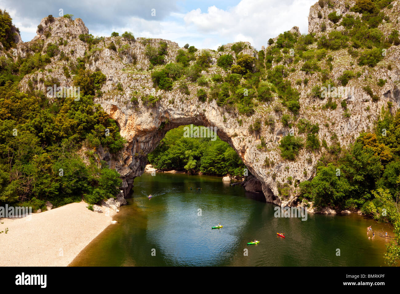 canoeing below the natural stone arch Pont d'arc across the Ardèche river - Stock Image