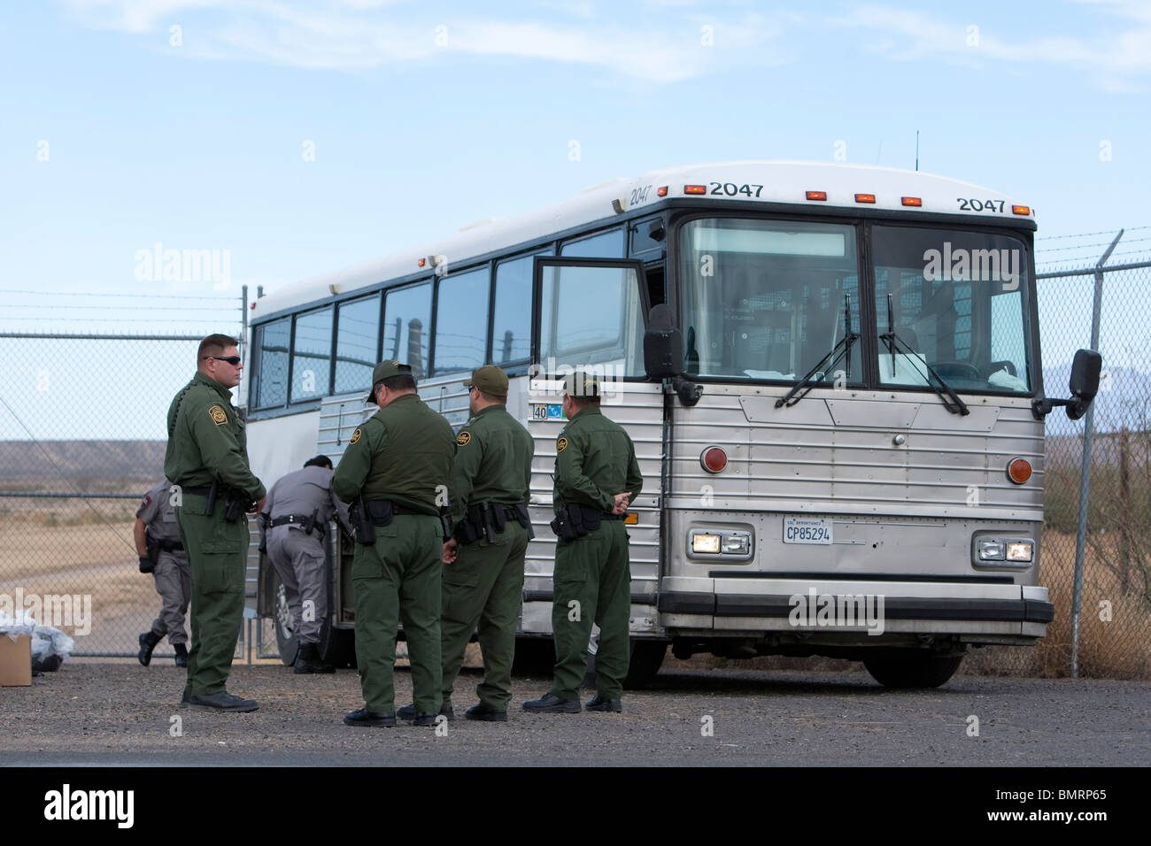 Security guards watch bus carrying Illegal aliens caught by the Department of Homeland Security who are being sent Stock Photo