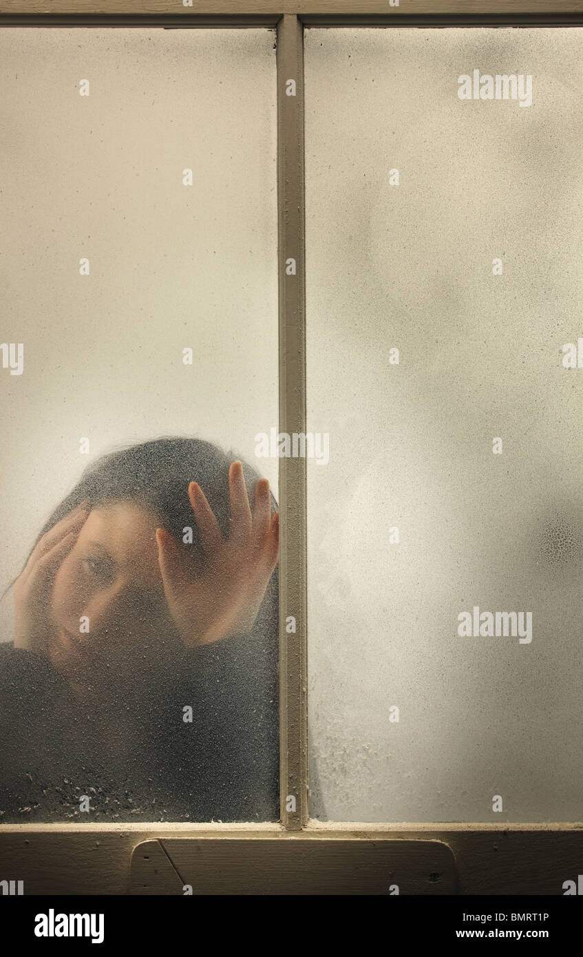 A Woman Behind A Cold, Frosted Window - Stock Image