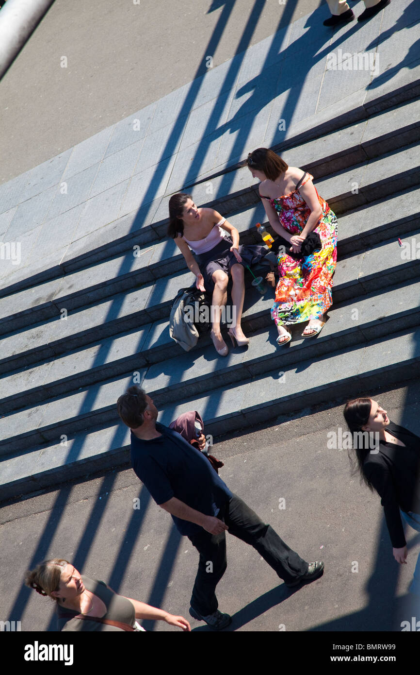 Sitting on steps in the sun, London, UK - Stock Image