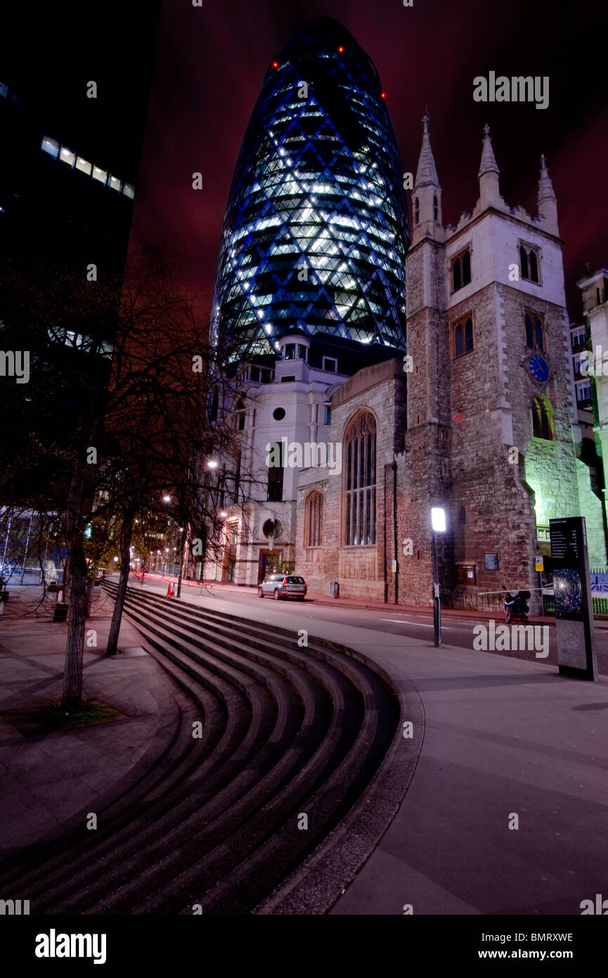 Swiss RE building at 30 St Mary Axe in the City of London as seen from Leadenhall Street at night. - Stock Image