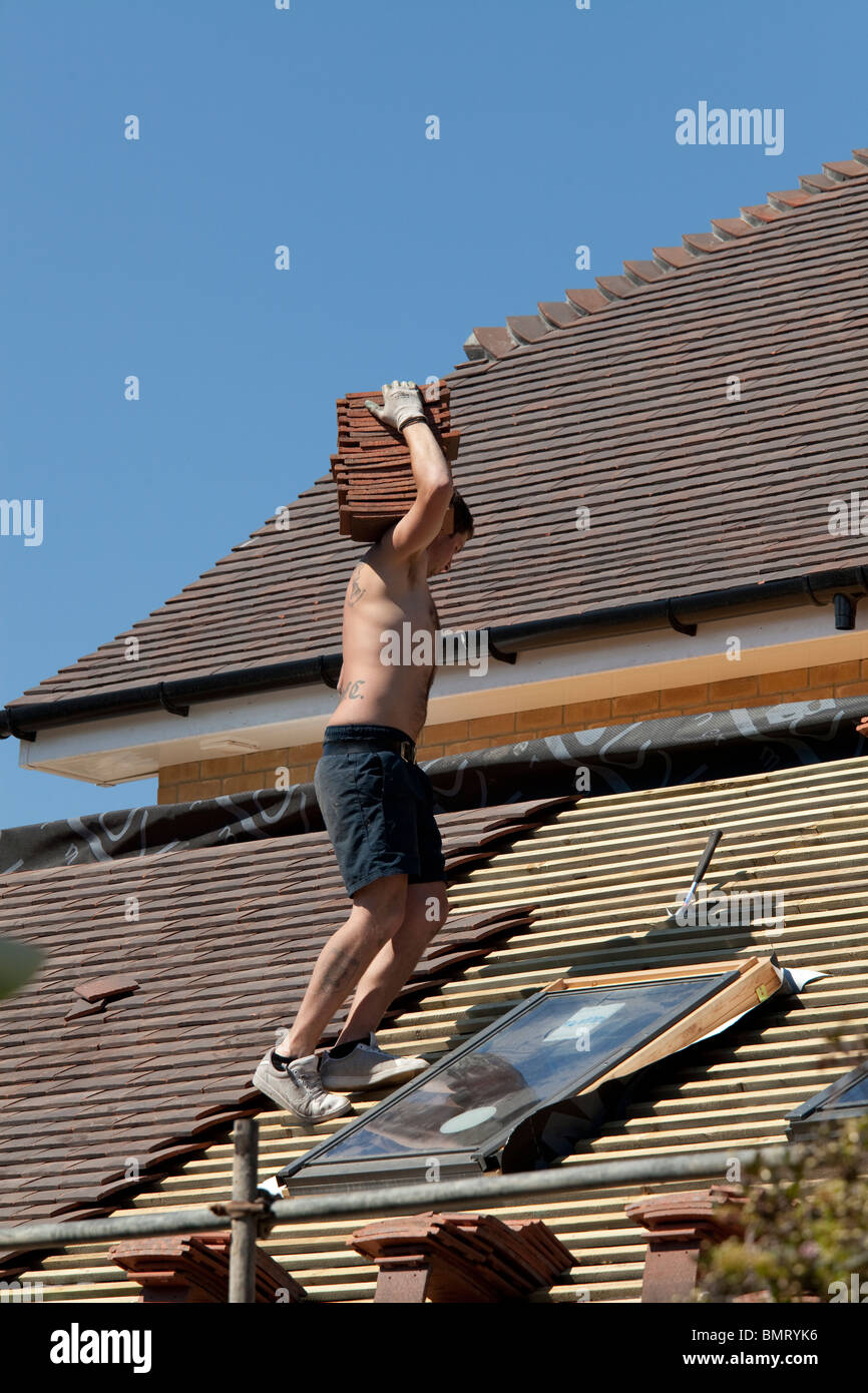 Roofer Wearing Only Shorts And Trainers Carrying Roof