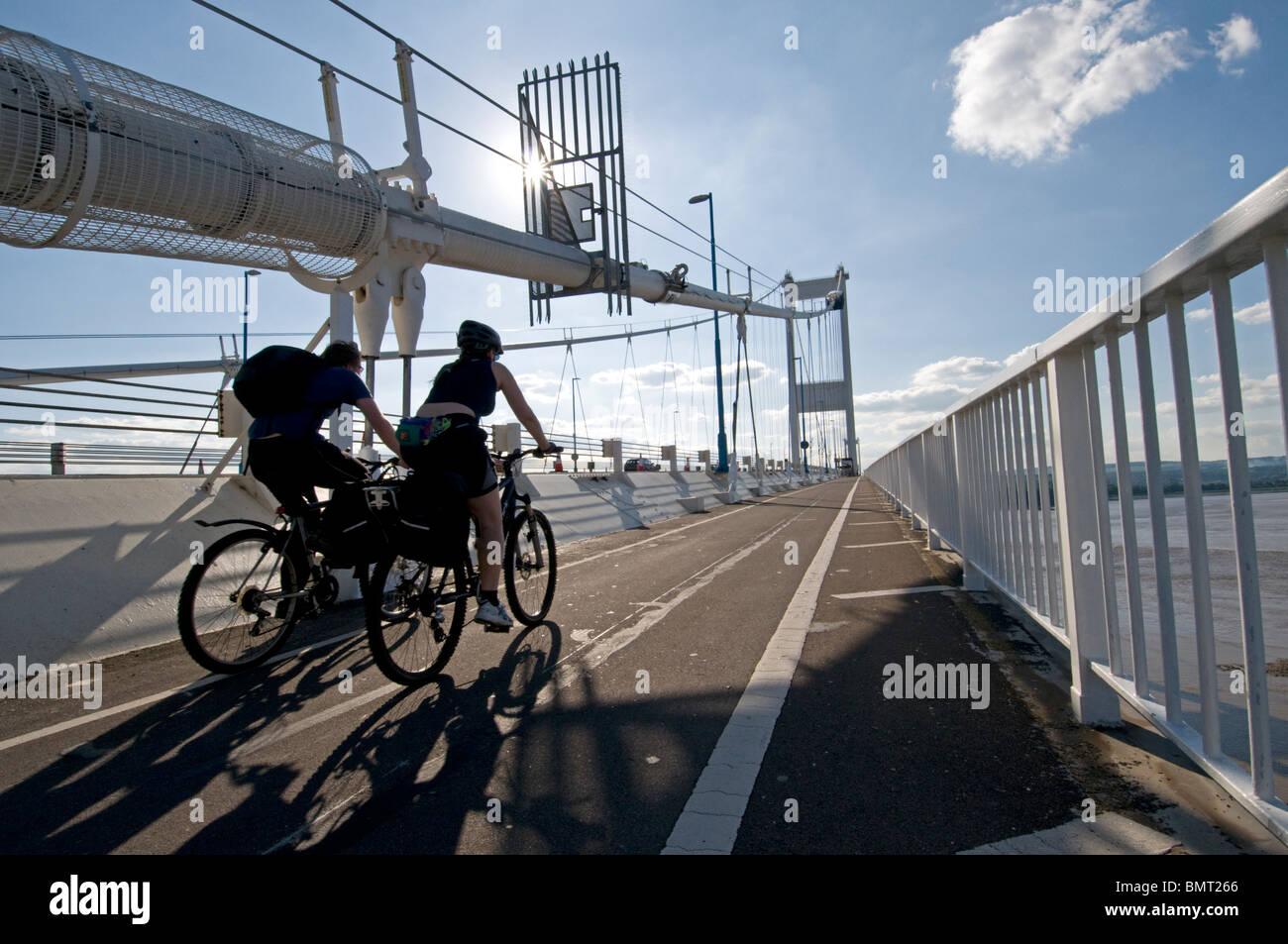 Two cyclists crossing the old Severn Bridge from England to Wales - Stock Image