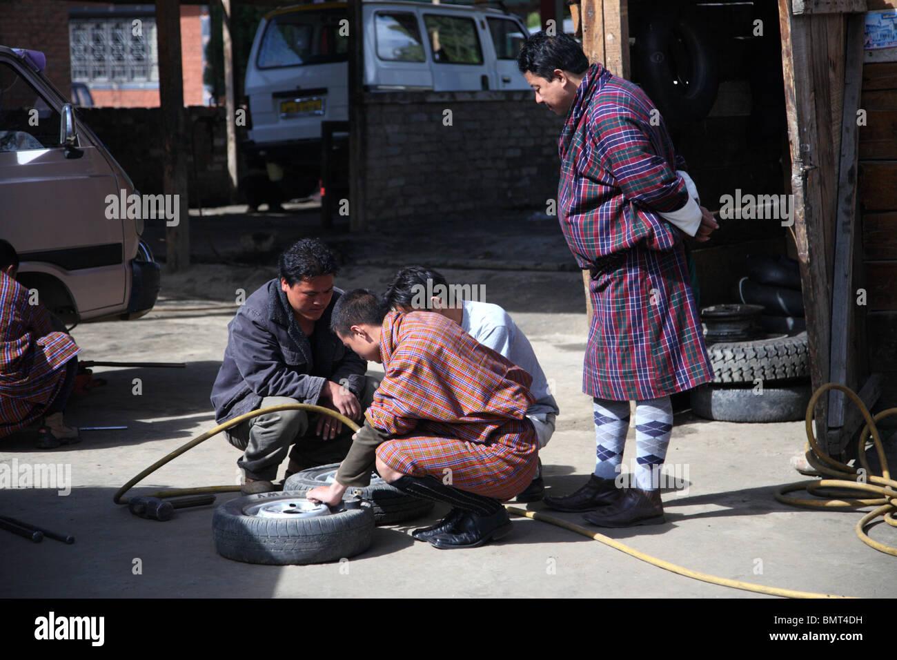 Car mechanics fixing a puncture in Paro, Bhutan. Stock Photo