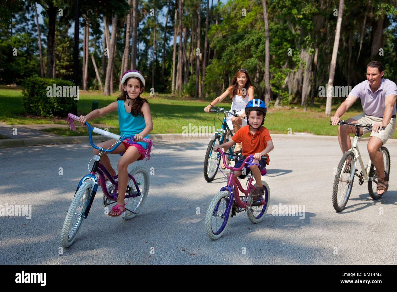 A modern family of two parents and two children, a boy and a girl, cycling together. - Stock Image