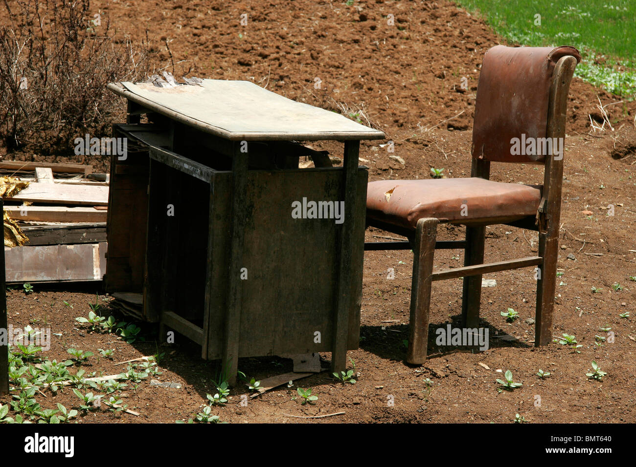 Manmade table and chair in broken stage arranged in nature - Stock Image